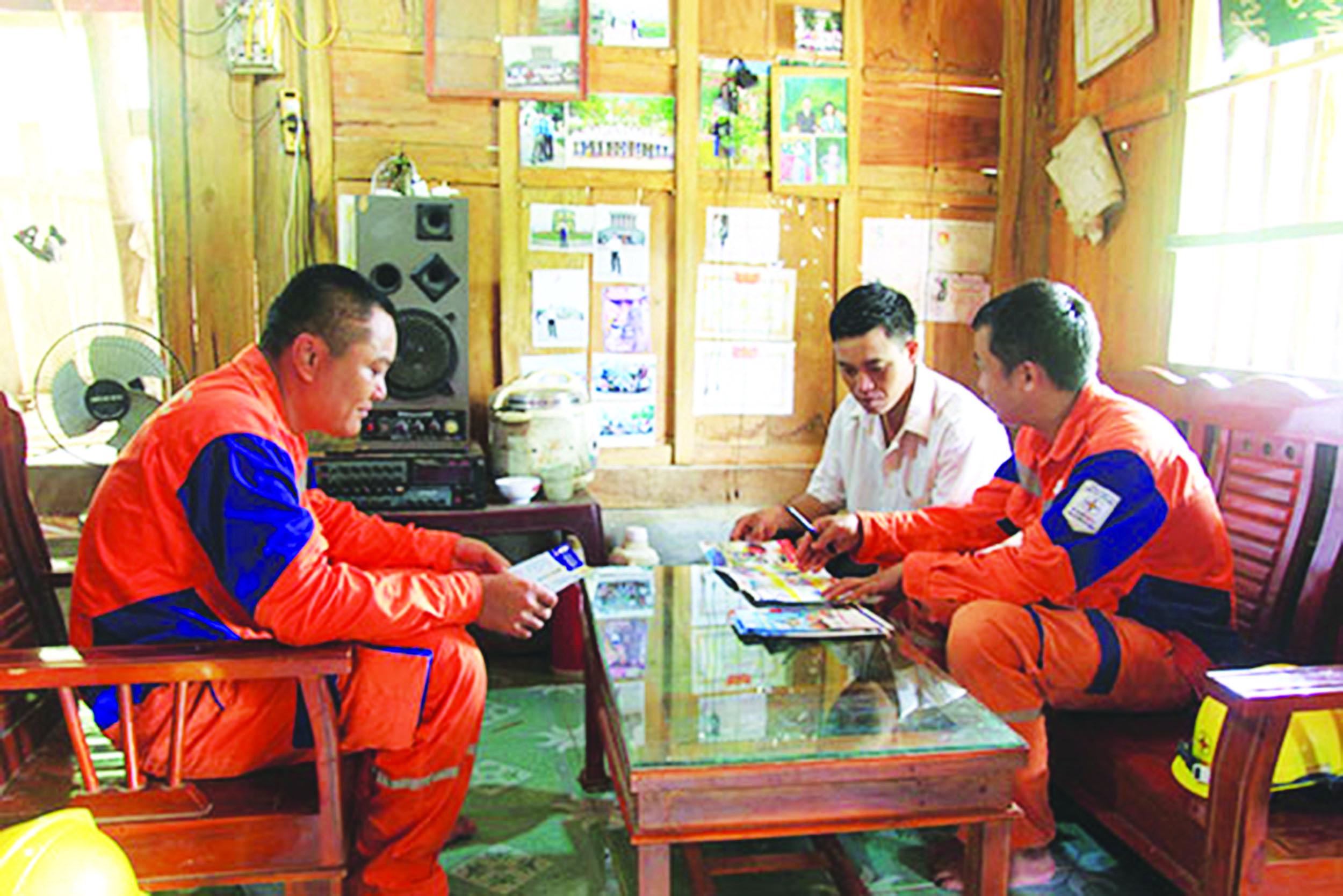 Công nhân Điện lực Mường La hướng dẫn người dân bản Nà Trà phương pháp sử dụng điện tiết kiệm, an toàn.