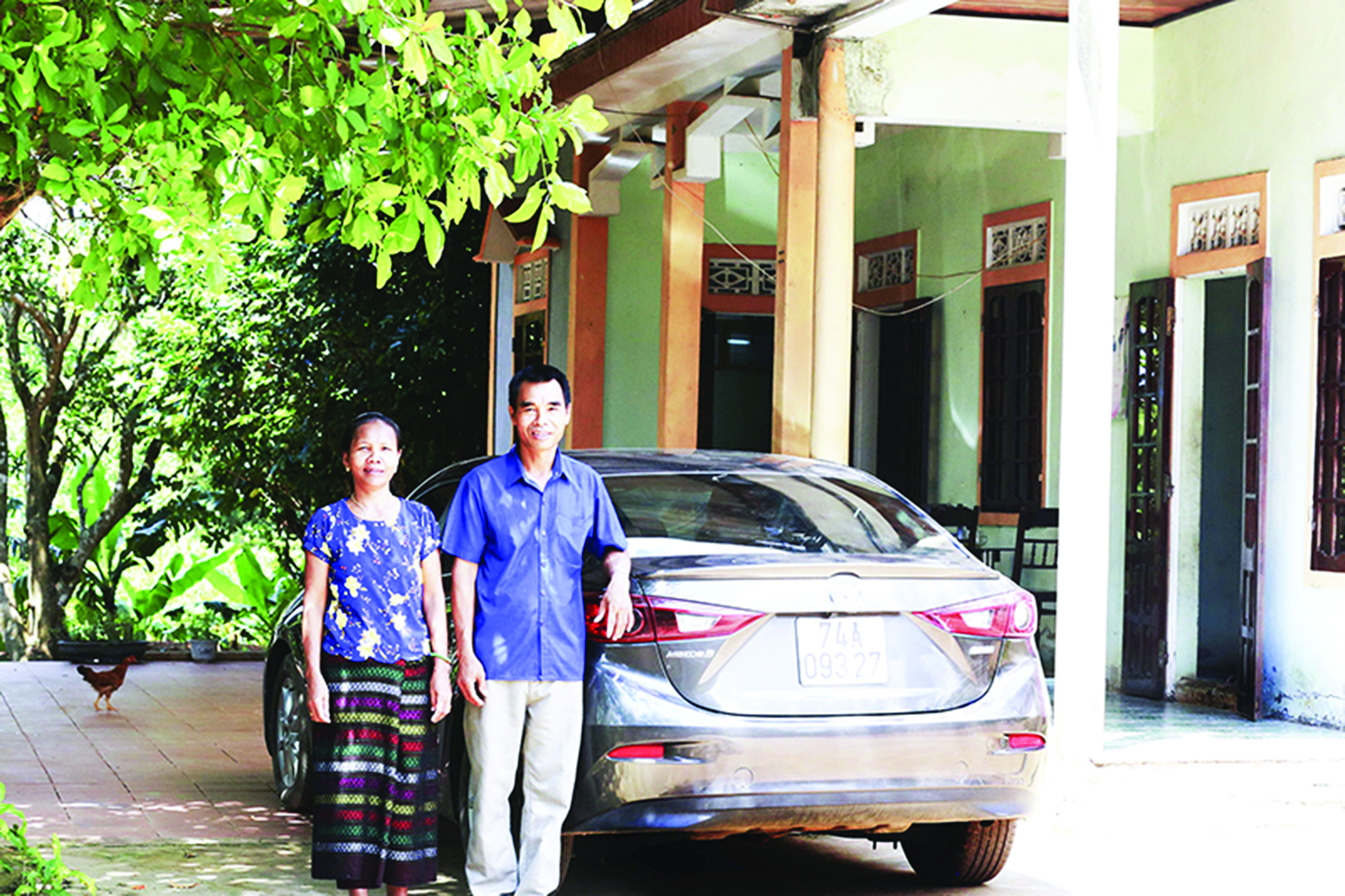 Vợ chồng ông Hồ Ngọc Trai bên chiếc xe ô tô và ngôi nhà khang trang.