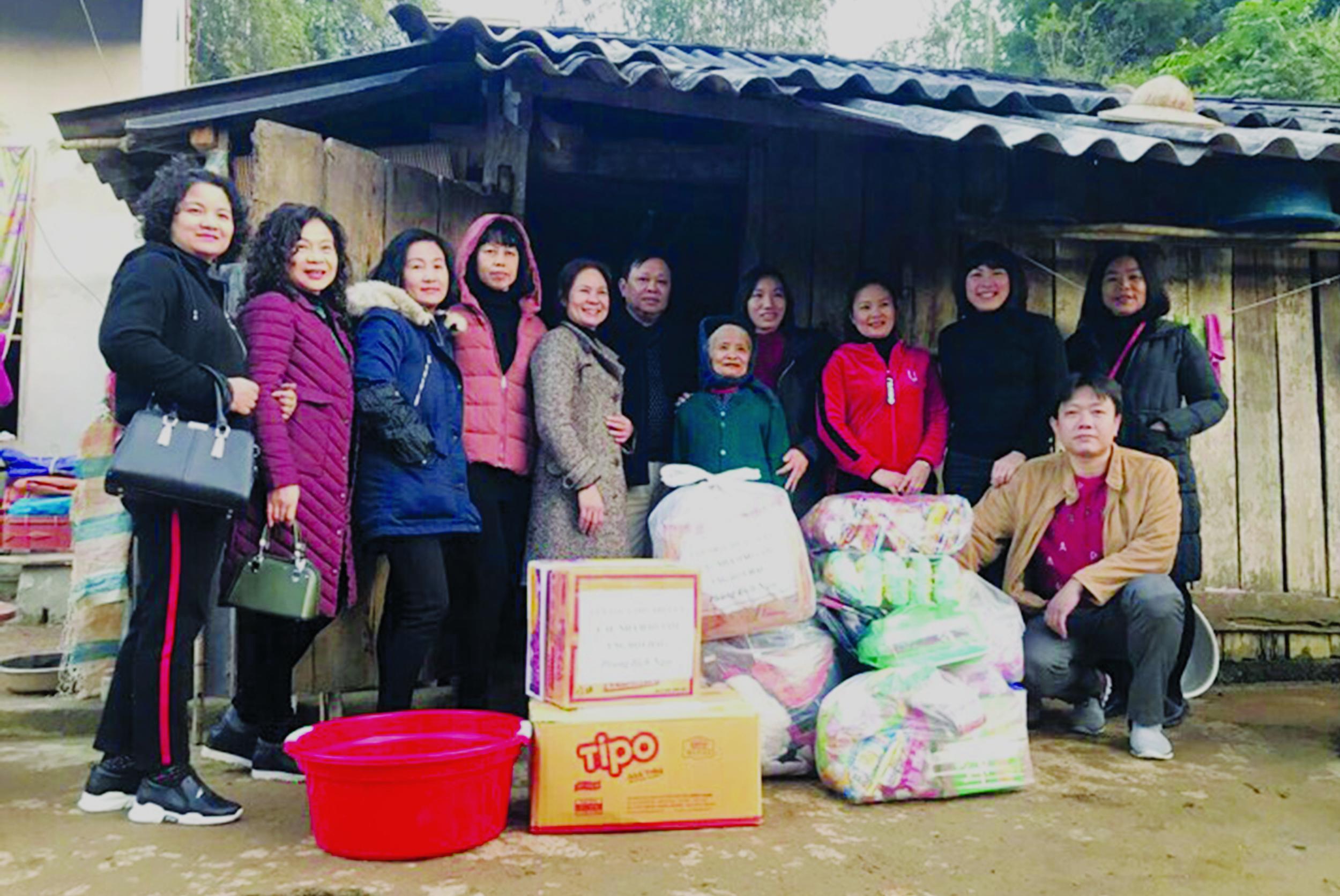 Ông Thảm (đứng thứ 6 từ trái qua) cùng các nhà hảo tâm trao quà cho người già ở xã Hoa Thám, huyện Bình Gia.