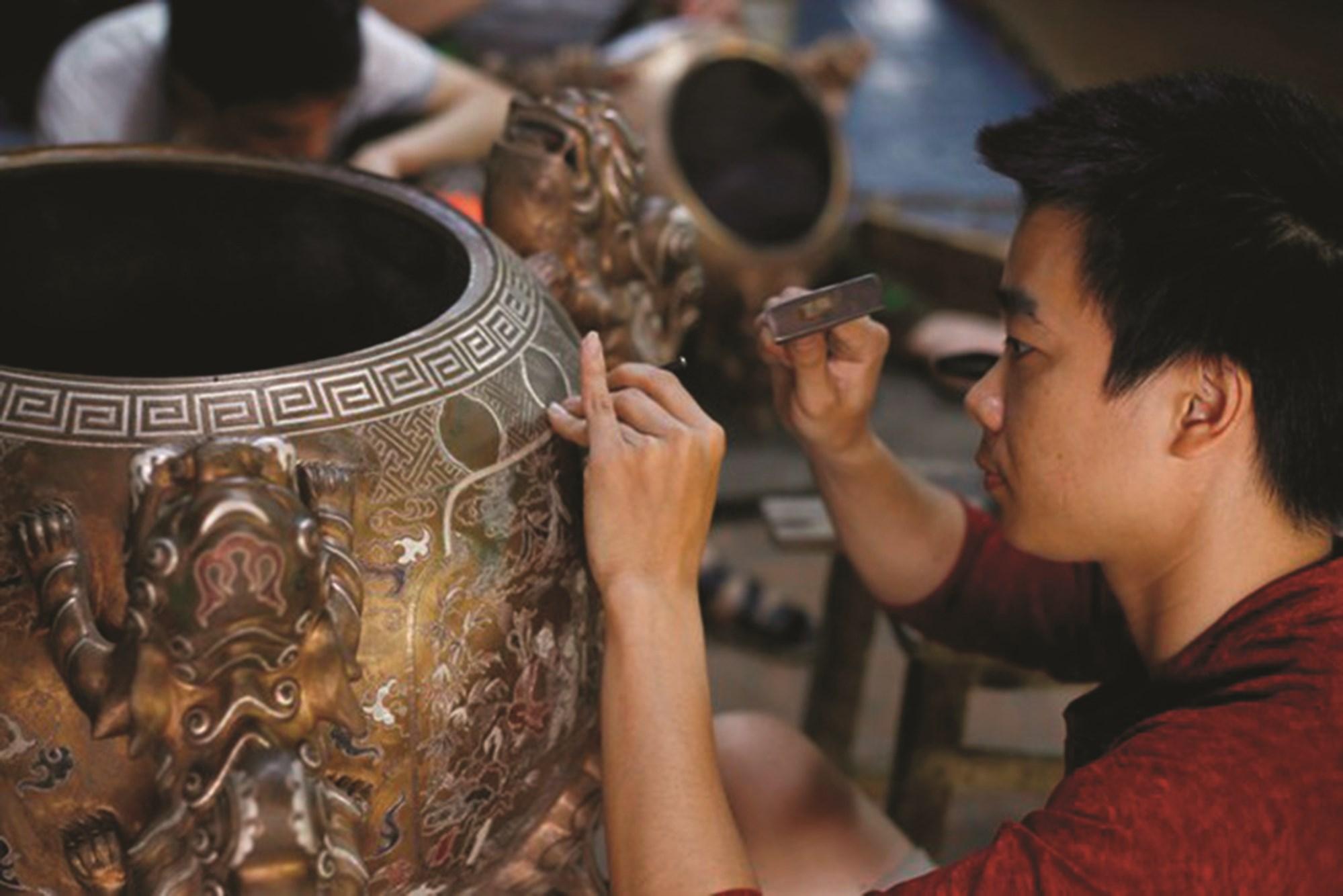 """Để có được những sản phẩm bằng đồng tinh xảo, đòi hỏi các nghệ nhân, người thợ làng Đại Bái phải có kinh nghiệm lâu năm, khéo léo, tỉ mỉ, tạo nên cái """"hồn"""" riêng cho mỗi sản phẩm"""
