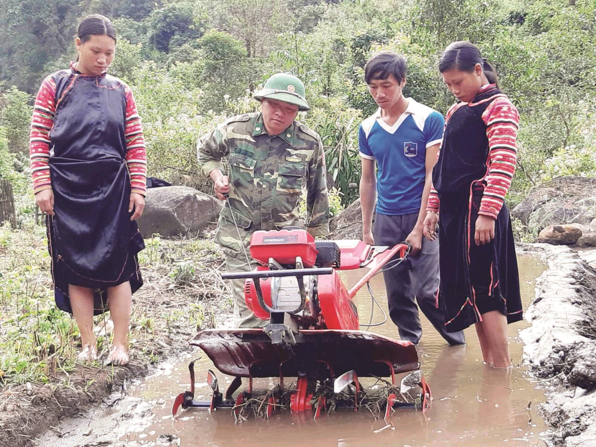 Bộ đội Biên phòng hướng dẫn người dân sử dụng máy cày làm đất trồng lúa nước.