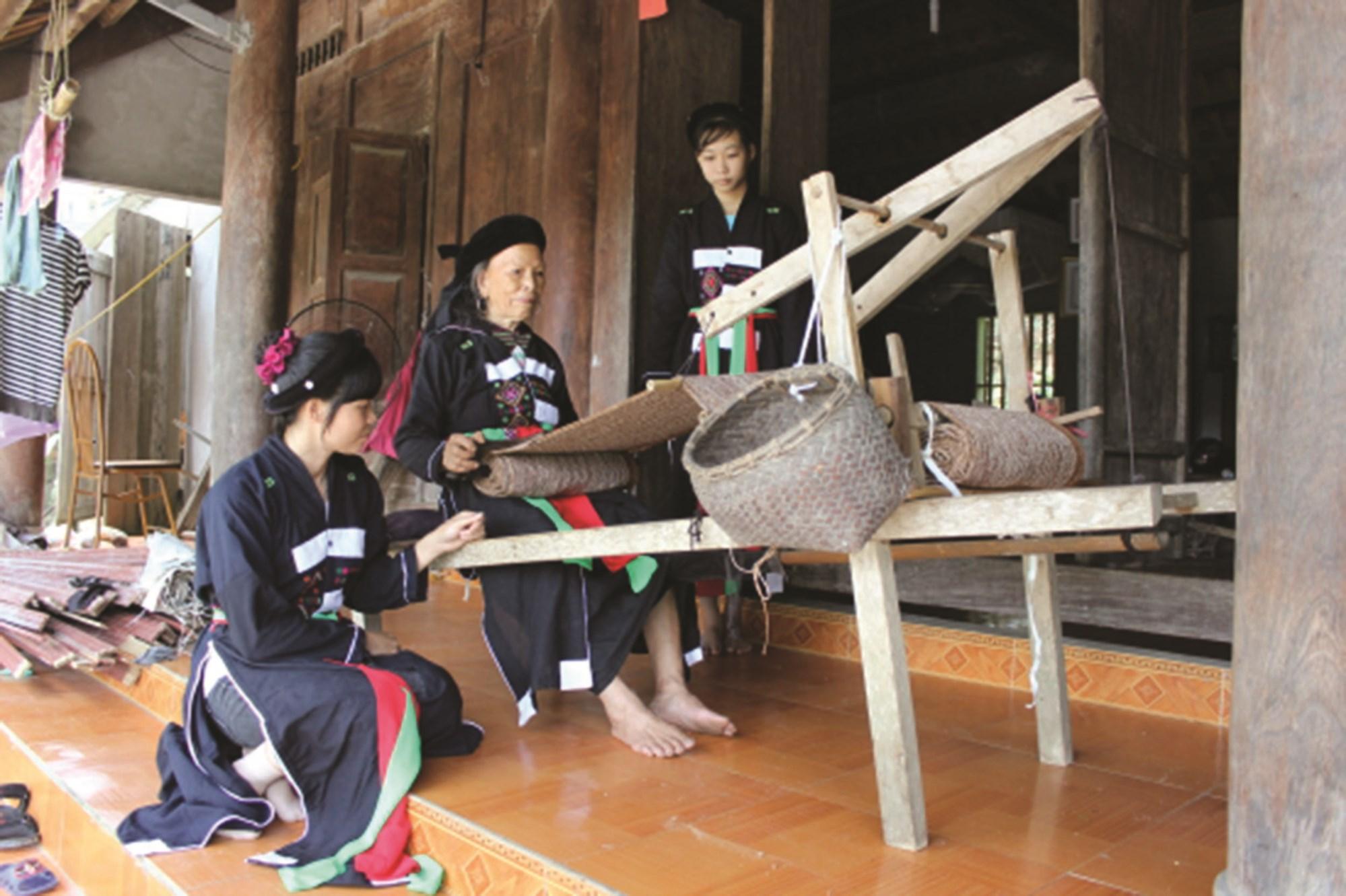 Nghệ nhân Trạc Thị Ngọn (ngồi giữa) hướng dẫn các hội viên cách dệt thổ cẩm