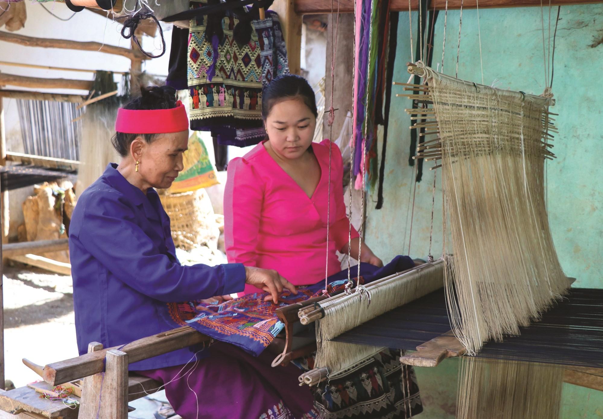 Dù tuổi cao nhưng hằng ngày bà Nút vẫn truyền dạy cách thêu dệt hoa văn cho các phụ nữ trong bản