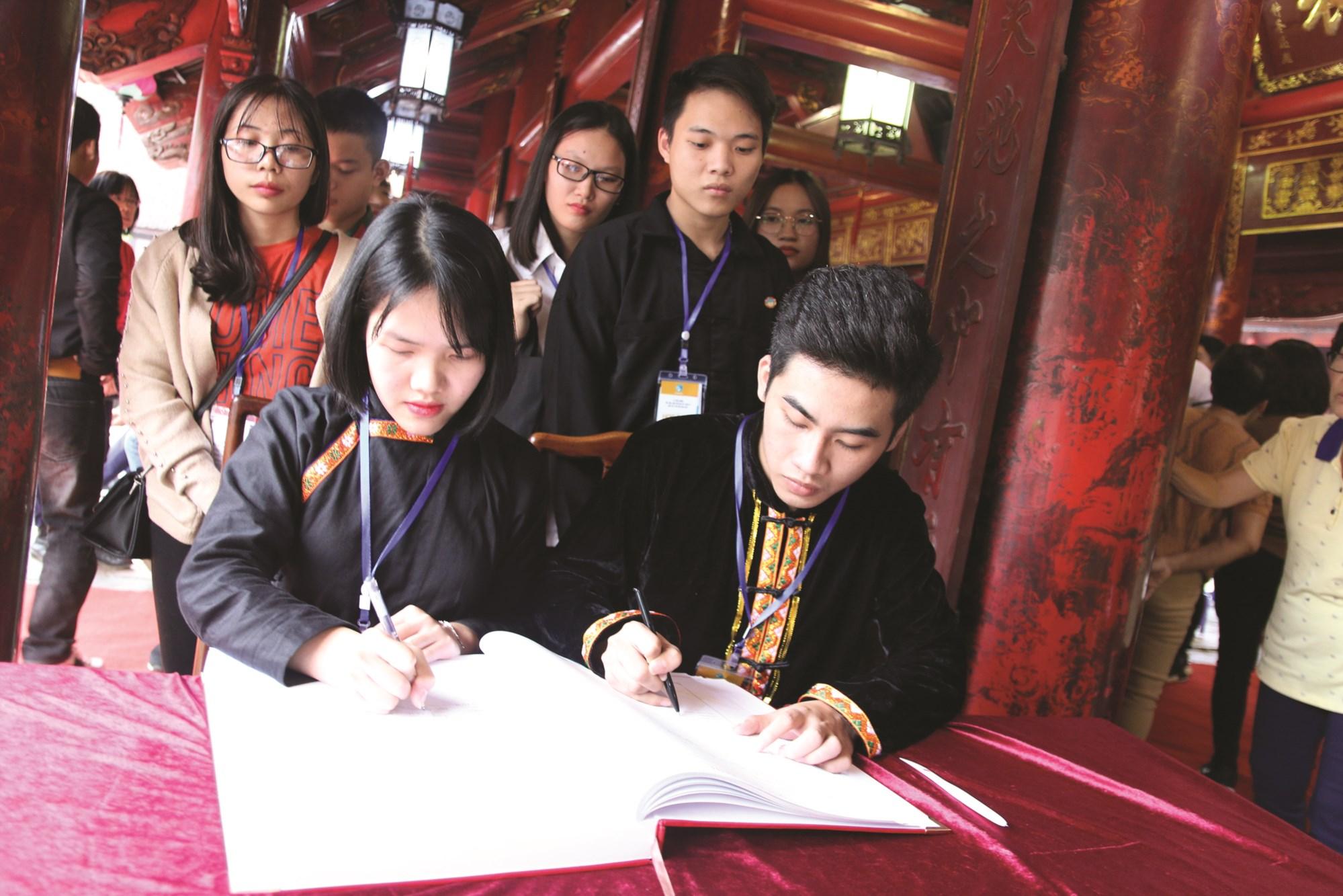 Các em học sinh, sinh viên DTTS xuất sắc, tiêu biểu ghi sổ vàng tại Văn miếu Quốc Tử Giám trong kỳ Tuyên dương năm 2018.