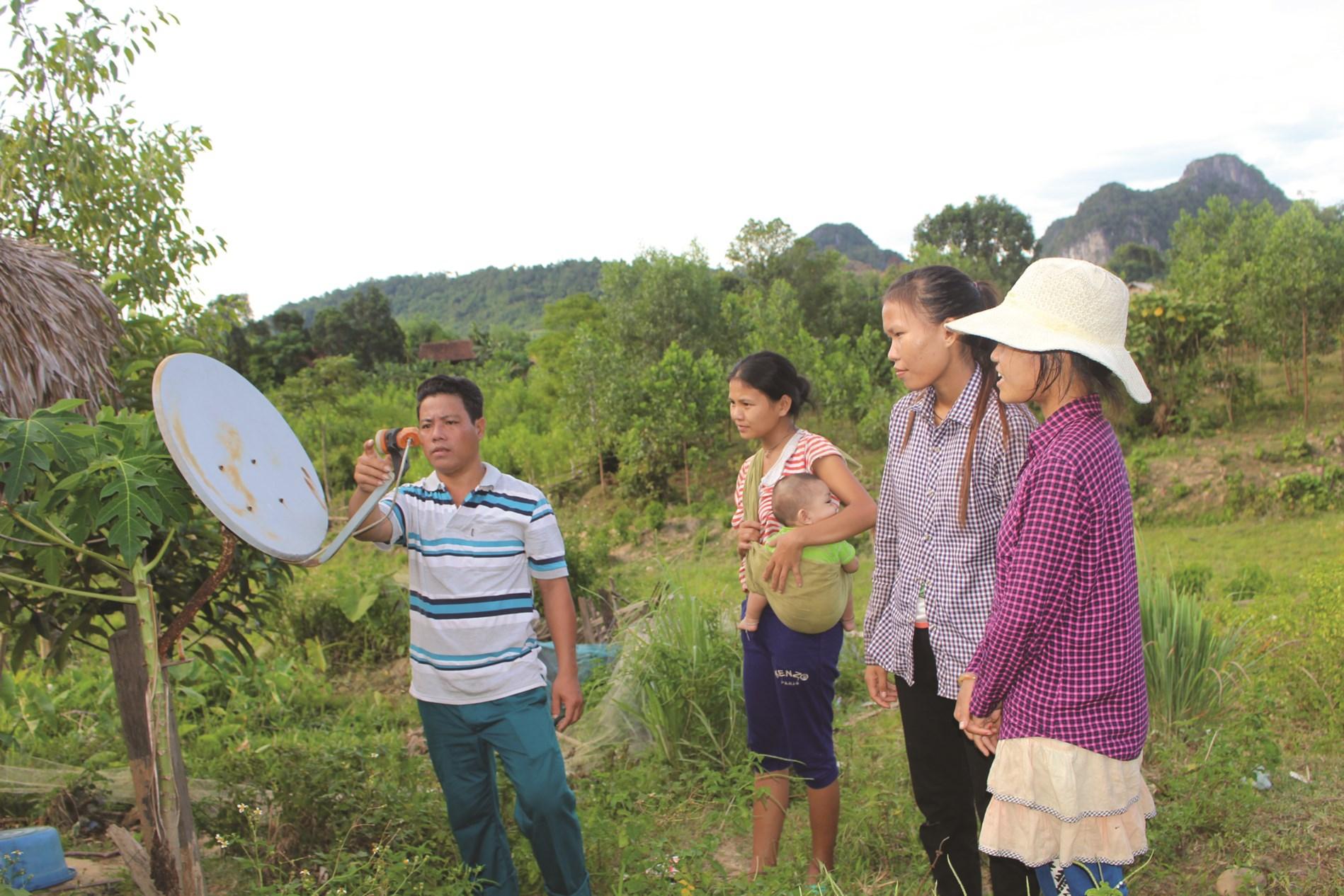 Cán bộ bản Kè, xã Lâm Hóa, huyện Tuyên Hóa hướng dẫn bà con người Mã Liềng sử dụng chảo thu sóng ti vi.
