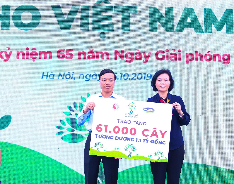 Bà Bùi Thị Hương, Giám đốc Điều hành Vinamilk trao bảng tượng trưng tặng 61.000 cây xanh của Quỹ triệu cây xanh cho Việt Nam cho đại diện TP.Hà Nội.