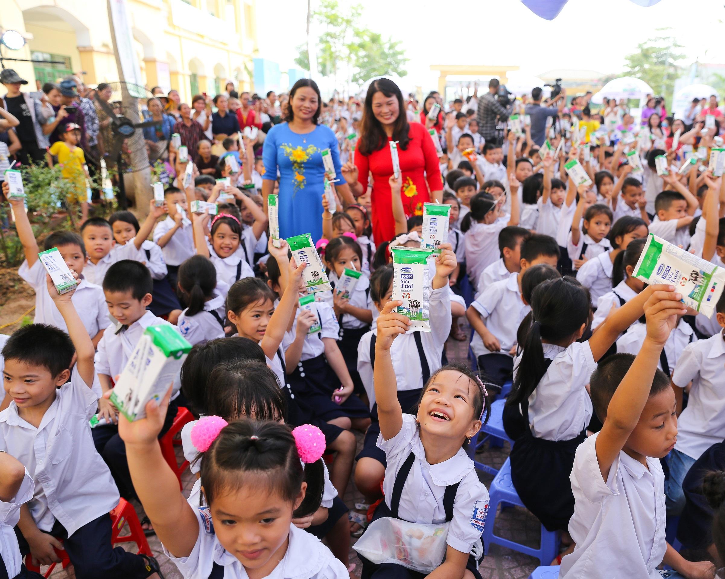 Niềm vui uống sữa của các em học sinh Hà Nội tại chương trình.