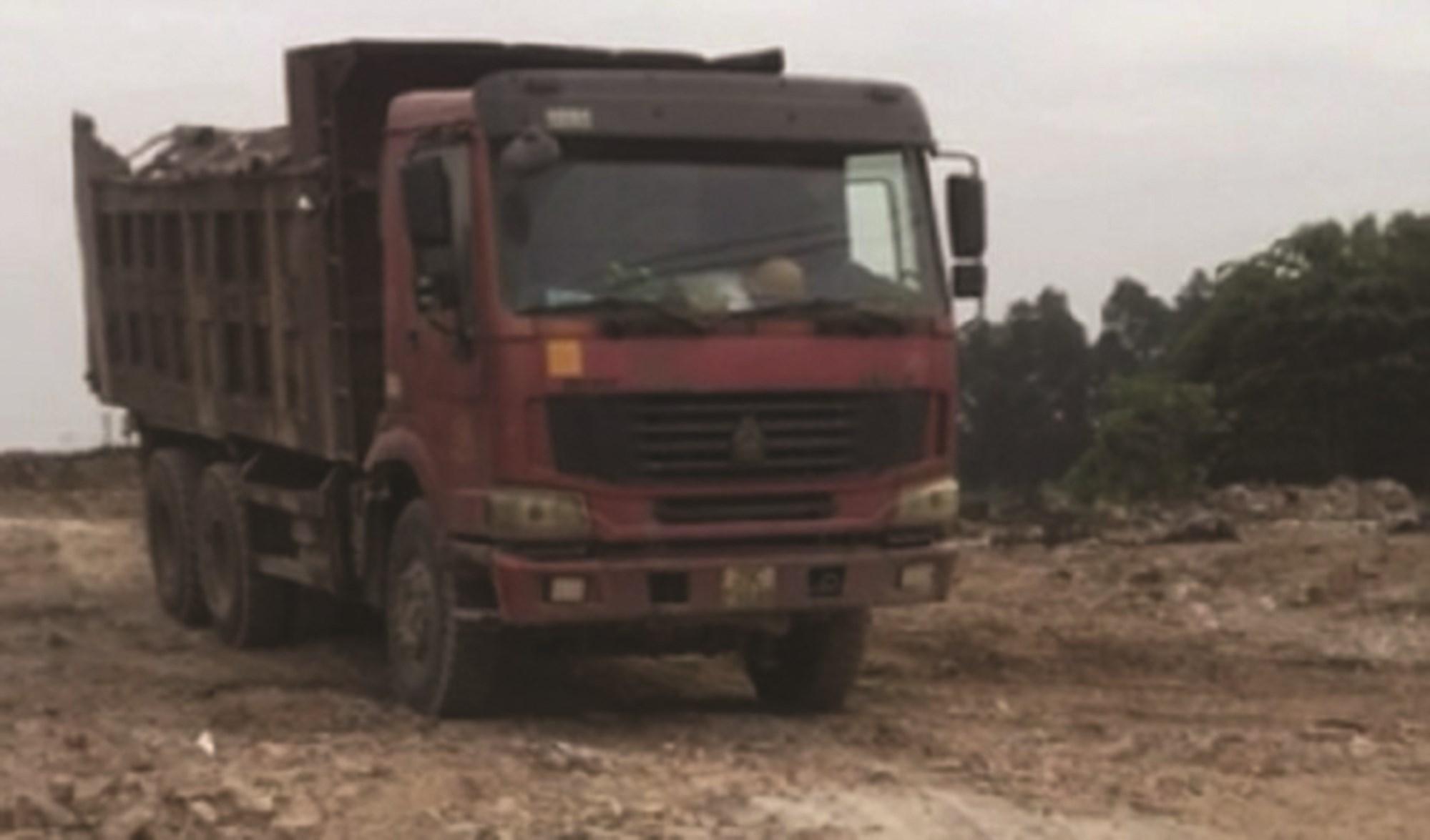 Những chiếc xe trọng tải lớn chở chất thải vào khu vực bãi đất phía sau trường tập bắn phường Yên Sở