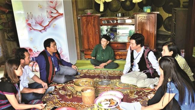 Già làng Kôn Pruôi (ngồi giữa) giới thiệu với khách đến thăm về âm điệu trầm hùng huyền bí của cồng, chiêng.