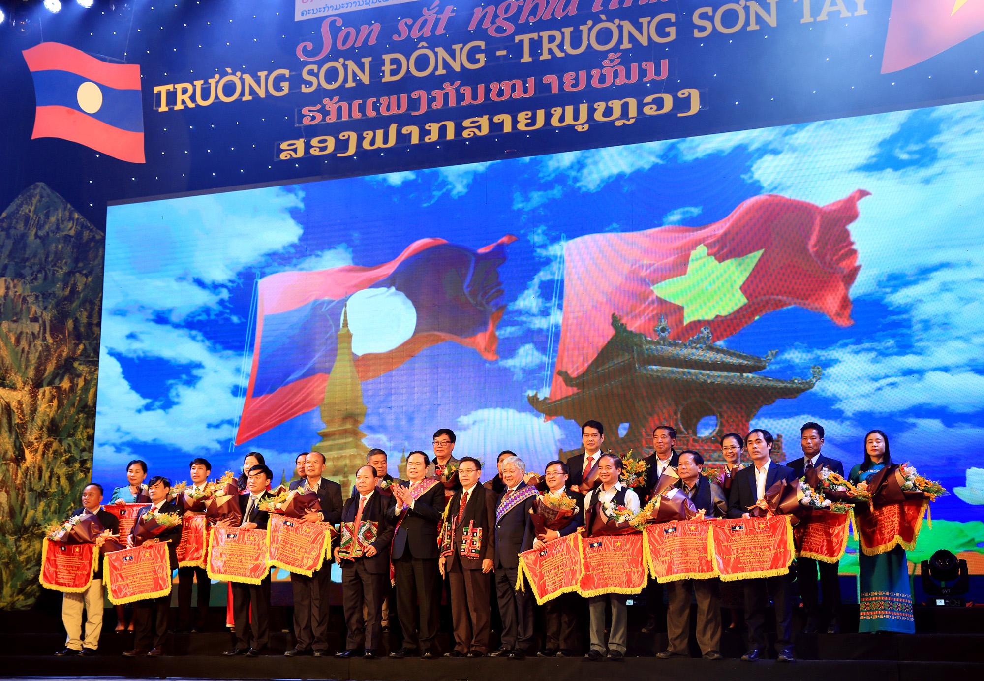 Các đồng chí lãnh đạo tặng Cờ lưu niệm cho đại diện các tỉnh Việt Nam và Lào tham gia Chương trình giao lưu Nhân dân giữa đồng bào DTTS, Người có uy tín sinh sống dọc tuyến biên giới Việt - Lào