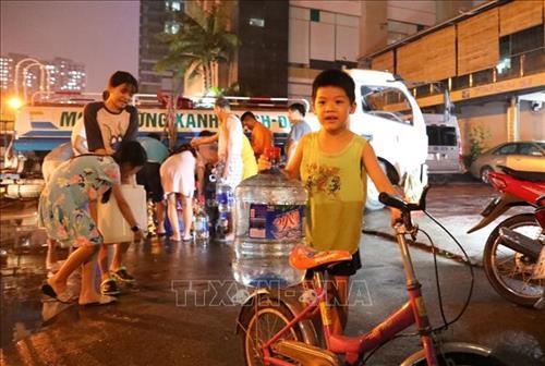 Các em nhỏ tại Khu đô thị Hapulico (Thanh Xuân Trung) phụ giúp người lớn lấy nước sạch lúc nửa đêm. Ảnh: Thành Đạt - TTXVN