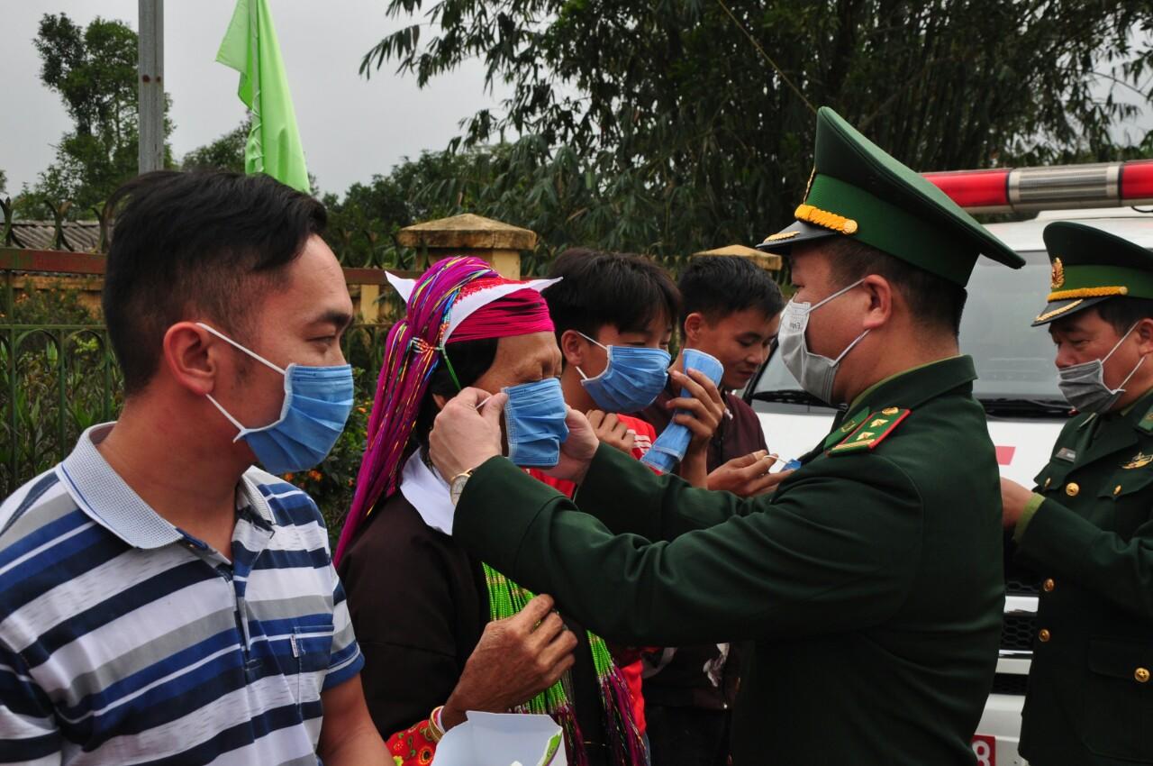 Các chiến sỹ Đồn Biên phòng Hoành Mô hướng dẫn đồng bào đeo khẩu trang đúng cách để phòng dịch