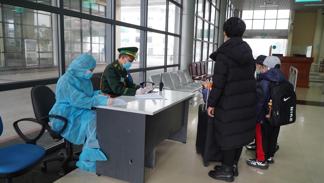 Bộ đội Biên phòng Quảng Ninh phối hợp với kiểm dịch y tế hướng dẫn người dân làm tủ tục kiểm soát y tế, đo thân nhiệt khi nhập cảnh qua cửa khẩu quốc tế Móng Cái
