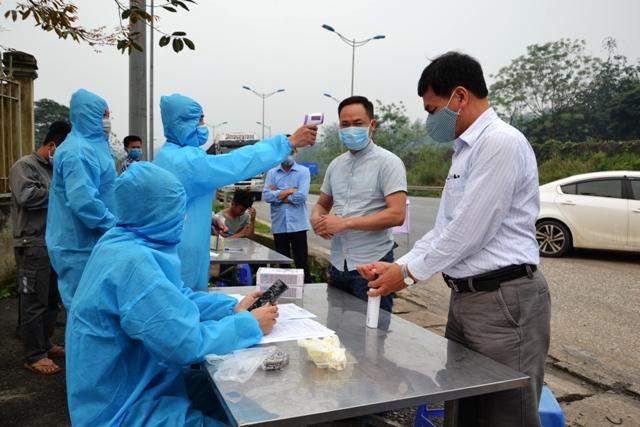 Lực lượng chức năng tại chốt kiểm soát đo thân nhiệt và hướng dẫn người dân rửa tay sát khuẩn