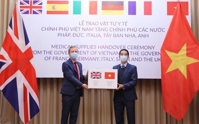 Thứ trưởng Bộ Ngoại giao Việt Nam Tô Anh Dũng trao tượng trưng 100.000 khẩu trang của chính phủ Việt Nam cho Đại sứ Anh tại Việt Nam Gareth Ward. Ảnh: Thông tấn xã Việt Nam.