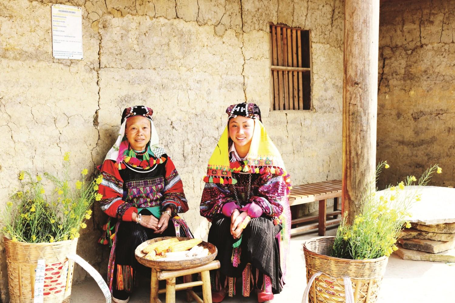 Phụ nữ dân tộc Lô Lô ngồi tẽ ngô trước cửa nhà