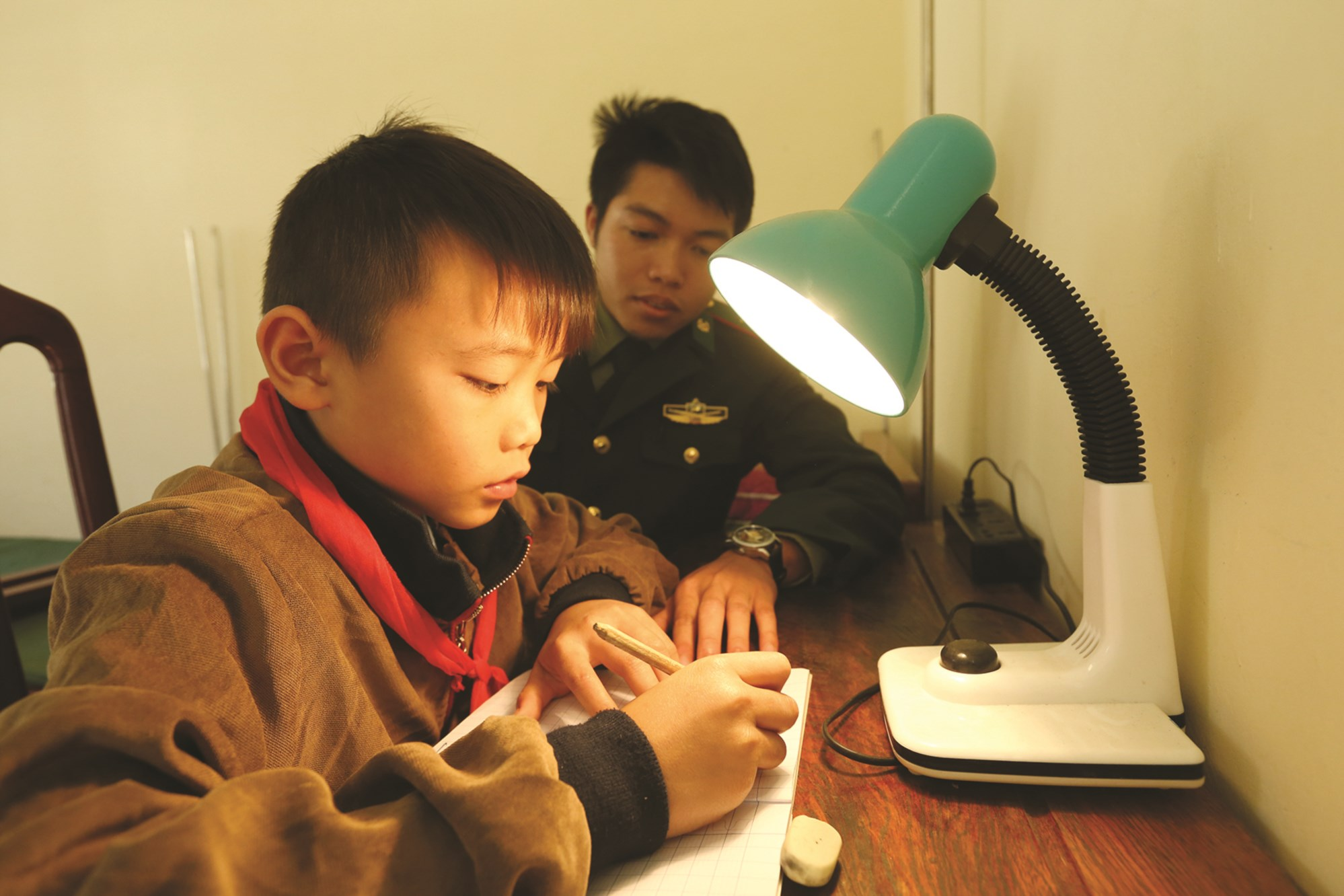 Cán bộ chiến sĩ ĐBP Pa Thơm hướng dẫn em Quàng Văn Kiên học bài.