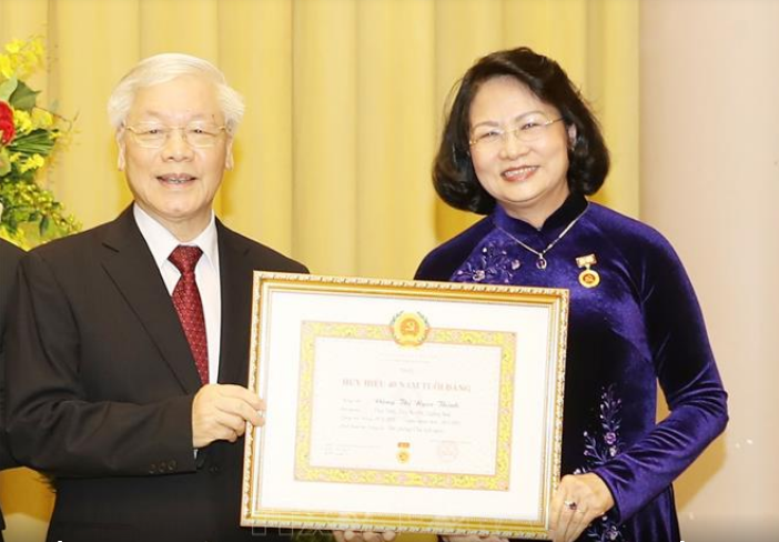 Tổng Bí thư, Chủ tịch nước Nguyễn Phú Trọng trao Huy hiệu 40 năm tuổi Đảng tặng đồng chí Đặng Thị Ngọc Thịnh. Ảnh: TTXVN