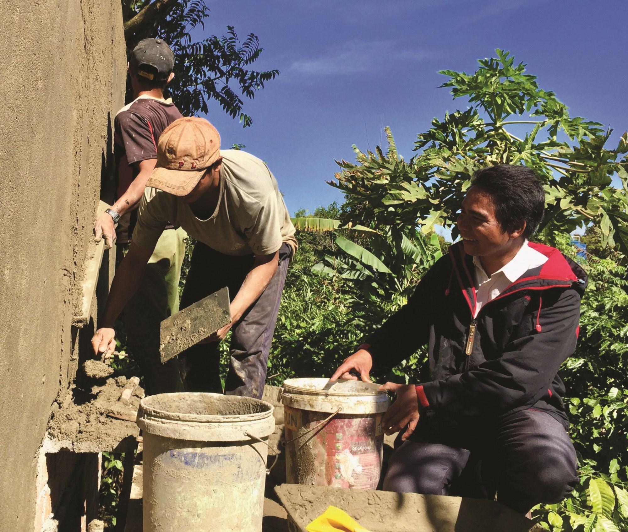 Anh Y Phô Niê (bìa phải) đang giám sát thi công nhà ở tại buôn Sah A. Ảnh T.Dũng