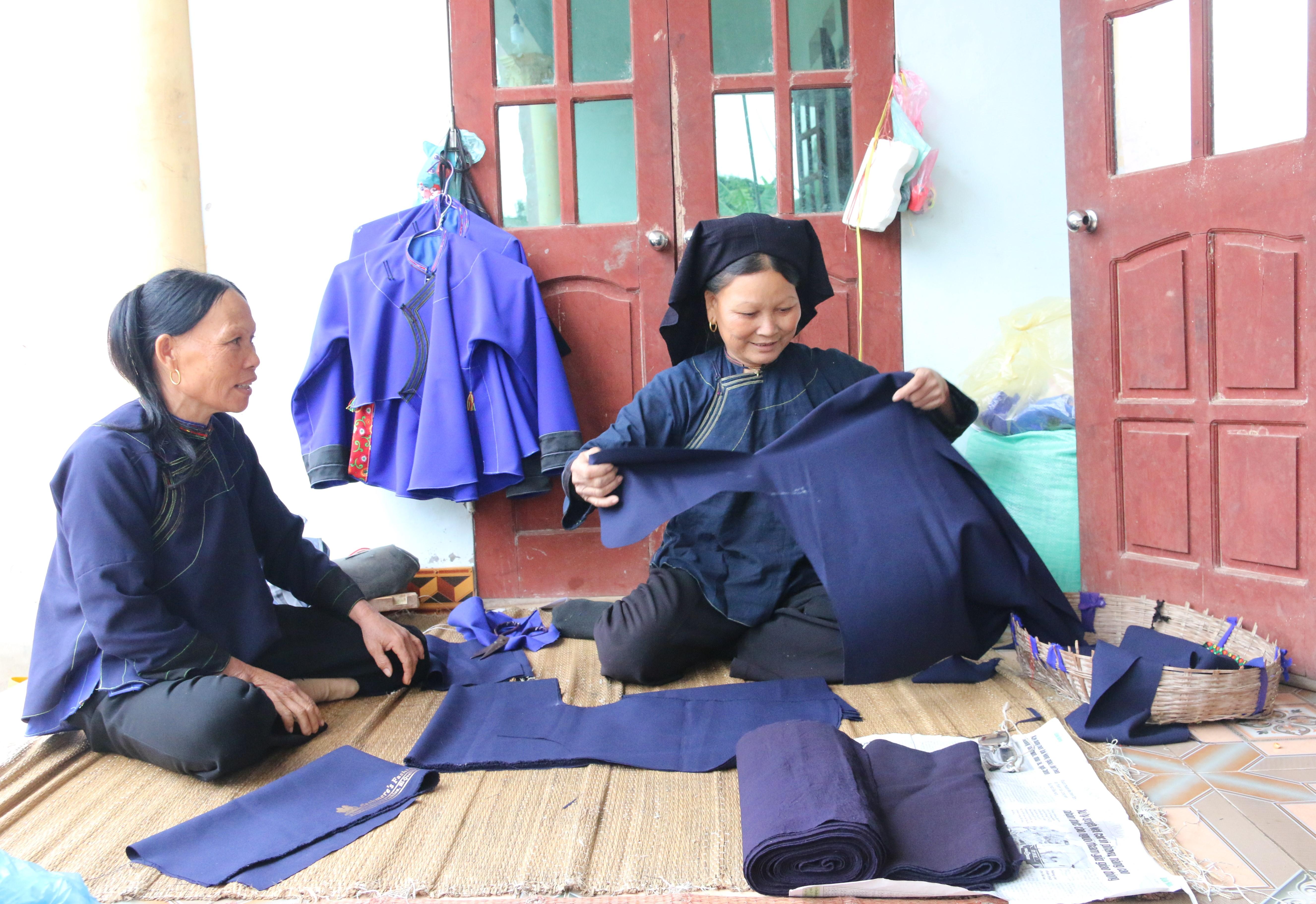 Bà Lăng Thị Liên (bên phải) đang cắt may trang phục dân tộc Nùng cho bà con trong thôn