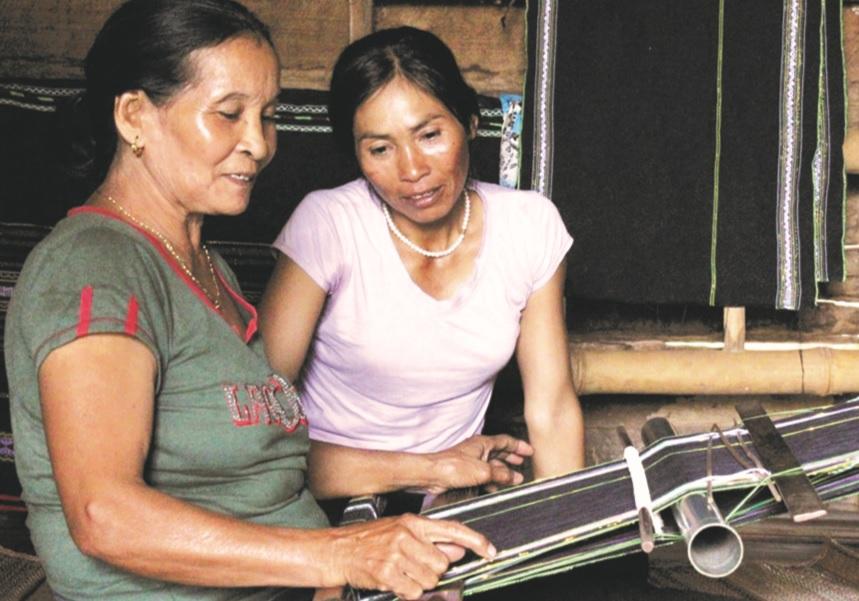 Bà H'Dleh Byă (bên trái) chỉ dạy cách dệt thổ cẩm cho con gái.