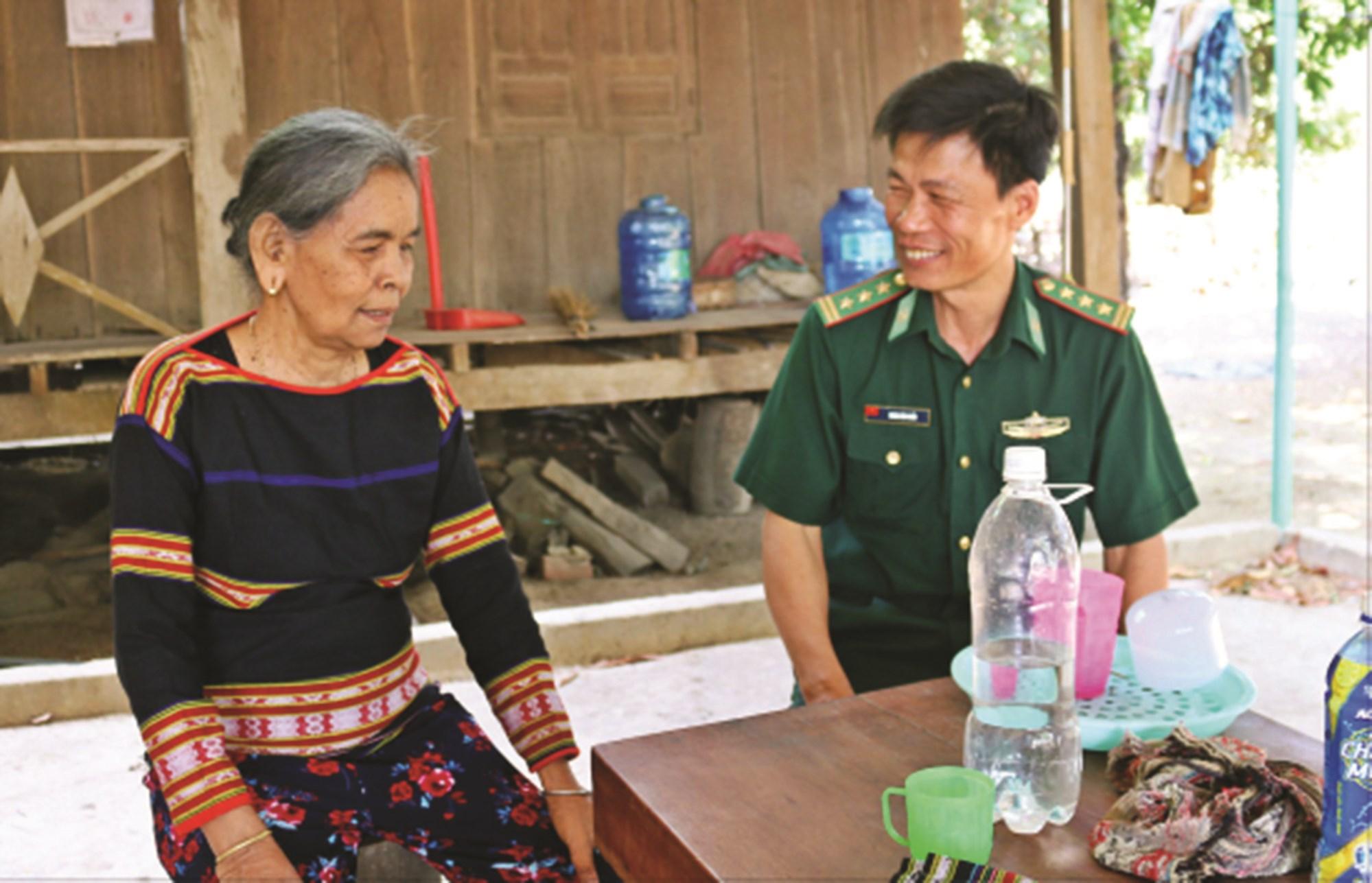 Già làng Ksor H'Blam trò chuyện với cán bộ Đồn Biên phòng Ia Mơr.