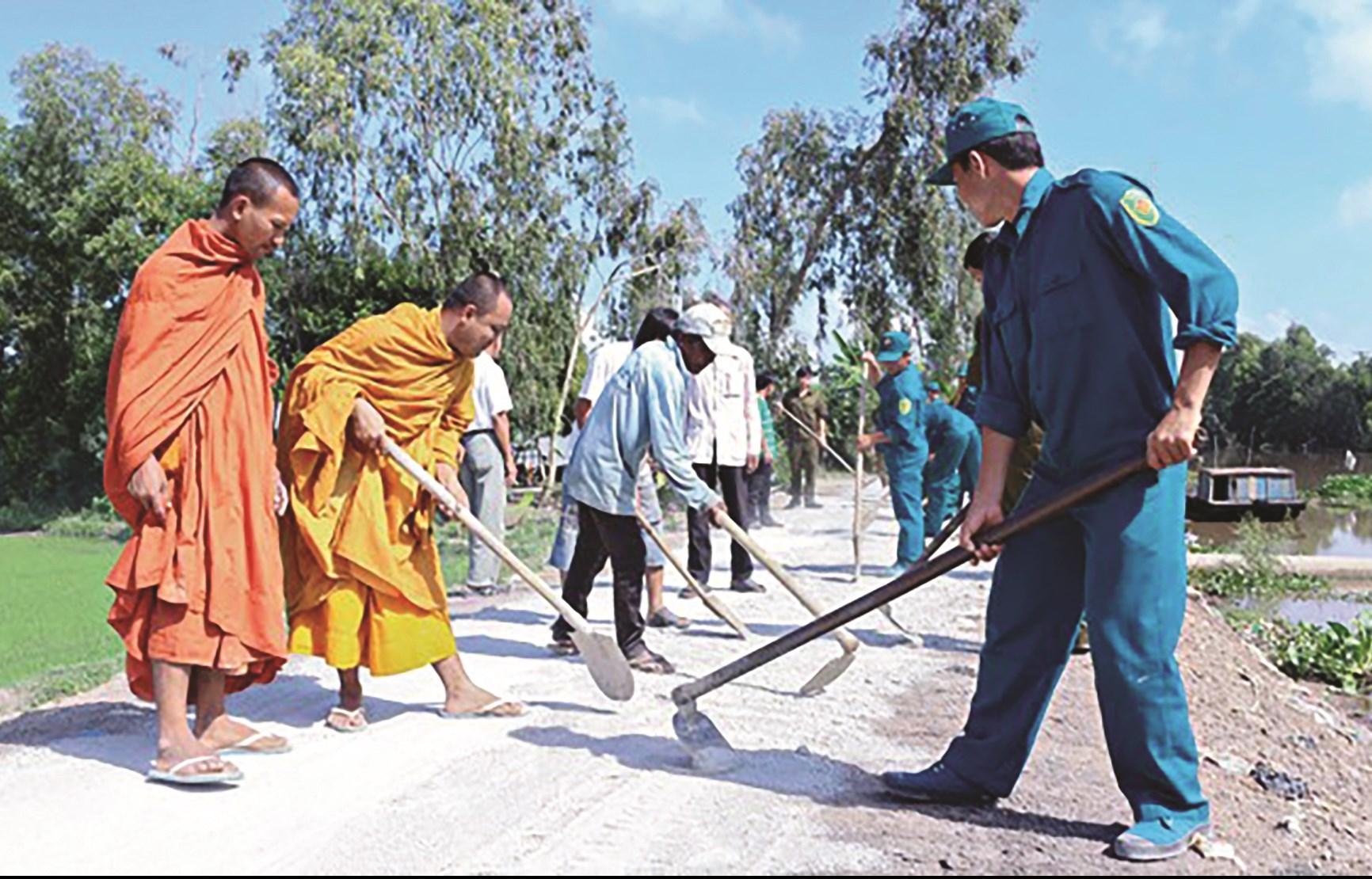 Các nhà sư - Người có uy tín trong cộng đồng dân tộc Khmer cùng người dân xây dựng đường giao thông nông thôn ở xã Cô Tô, huyện Tri Tôn (An Giang). Ảnh: TL