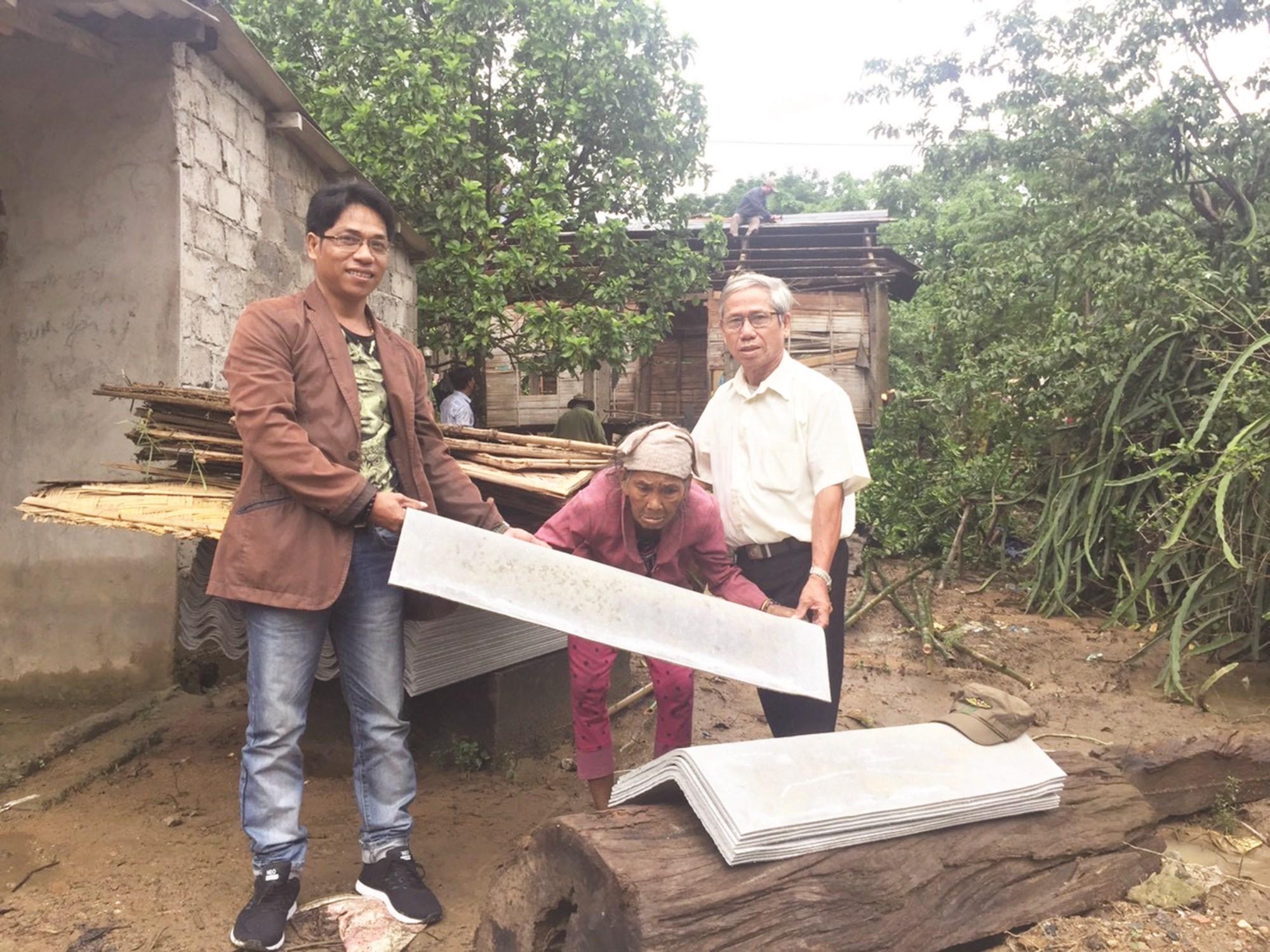 Anh Lê Xuân Hải trao tặng tấm lợp cho bà Pi Lâm (bìa trái), ngụ xã Đakrông, huyện Đakrông (tháng 5/2019).