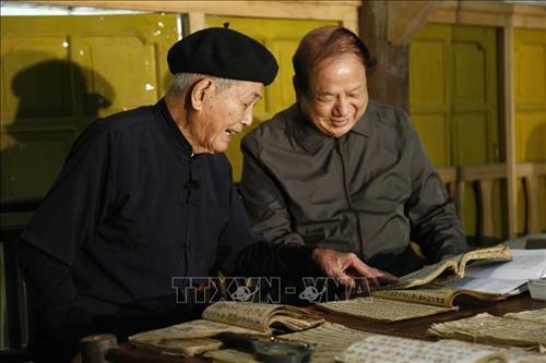 Ông Vân cùng nhà nghiên cứu văn học nghệ thuật Tống Đại Hồng. Ảnh: Nam Sương - TTXVN
