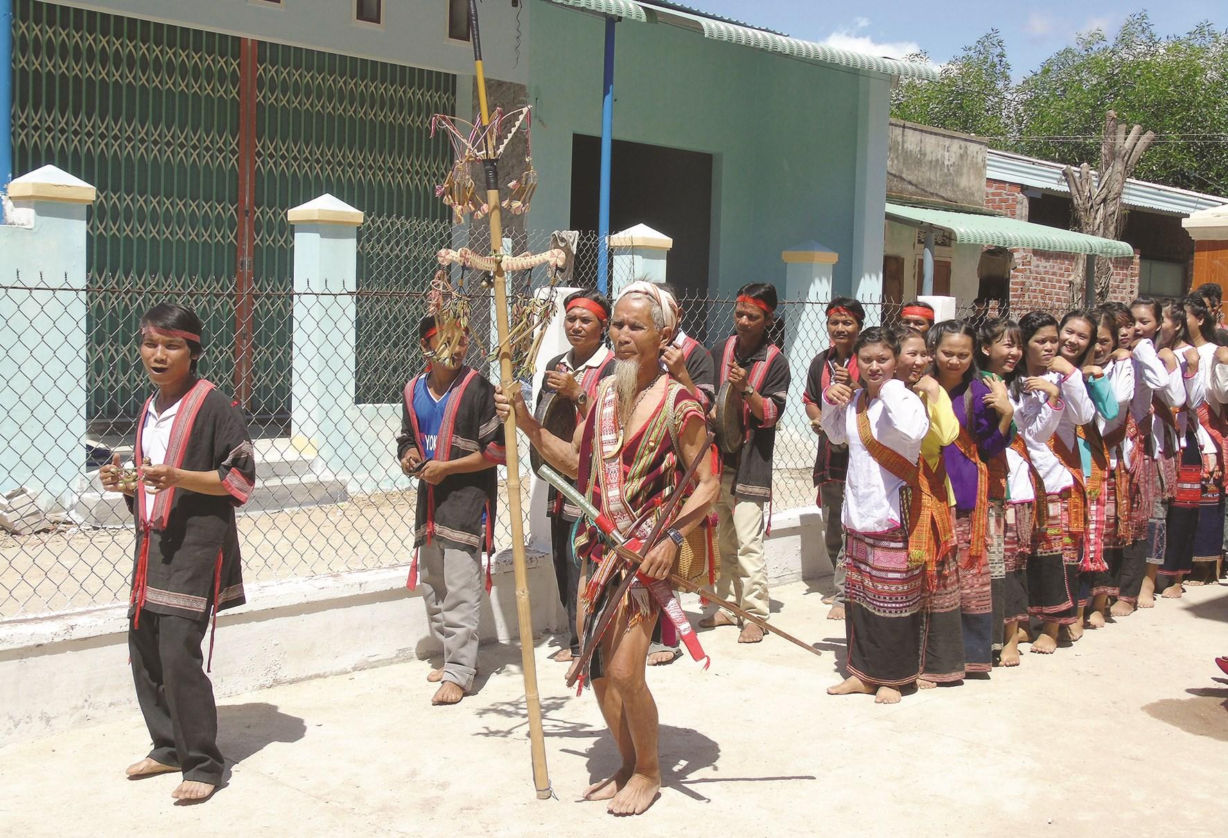 Nghệ nhân Lê Văn Ru (người cầm cây nêu) hướng dẫn bà con đánh cồng chiêng và múa xoang