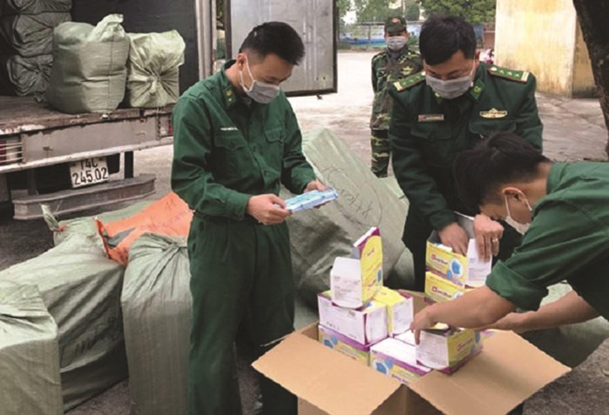 Lực lượng chức năng kiểm tra, thu giữ tang vật một vụ xuất lậu khẩu trang