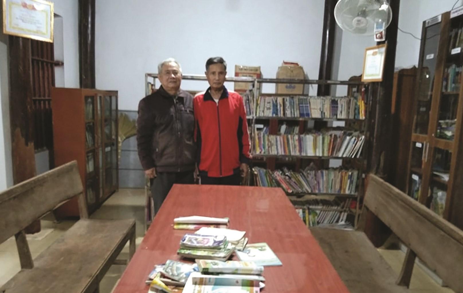Ông Bùi Văn Thống (trái) trong thư viện của xóm do chính ông dành nhiều tâm huyết xây dựng.