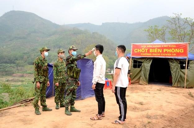 Các cán bộ, chiến sỹ đo thân nhiệt và hướng dẫn người dân địa phương các biện pháp phòng, chống dịch