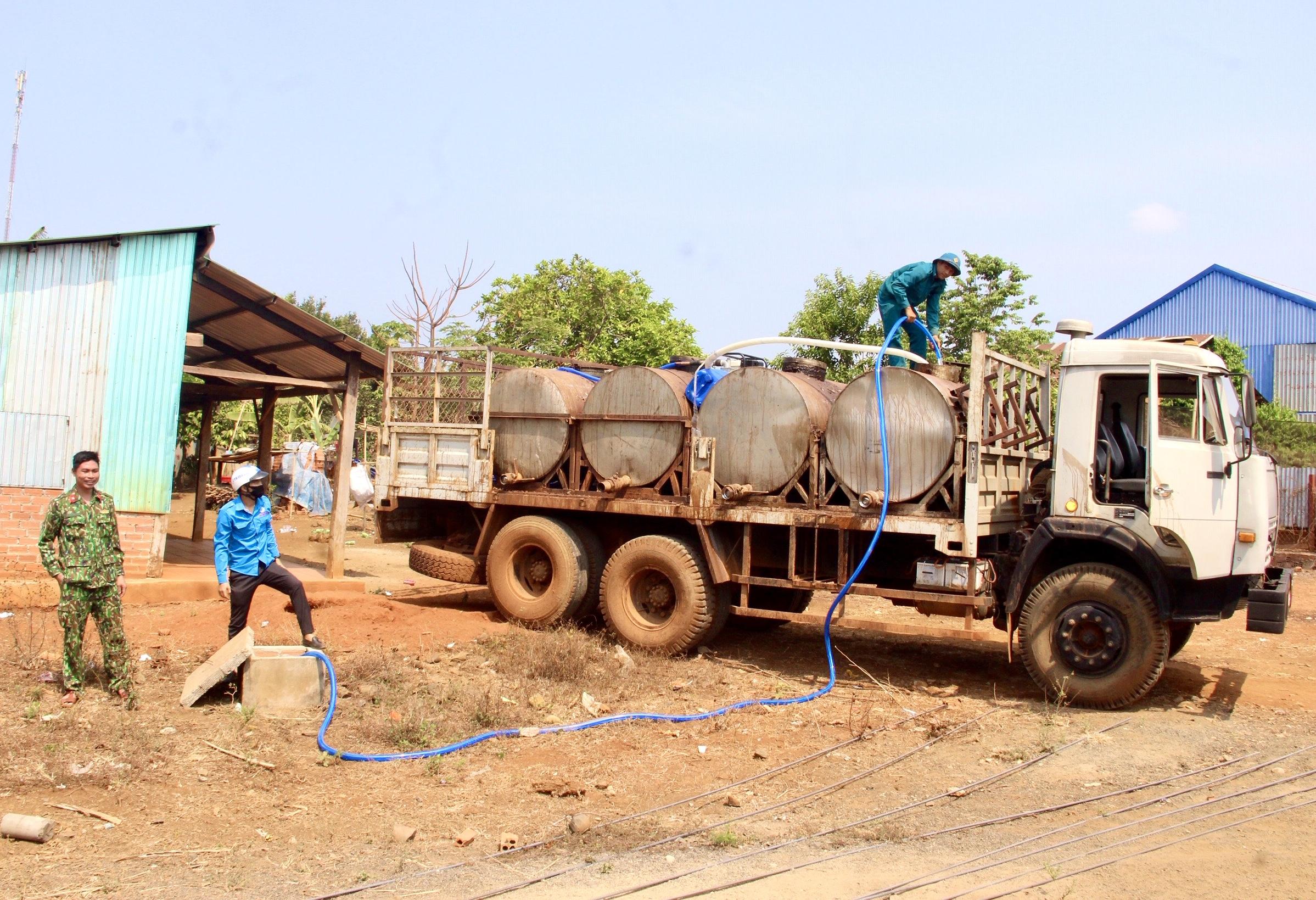 """Các cán bộ, chiến sĩ Đoàn Kinh tế - Quốc phòng 778 phối hợp với các lực lượng bơm nước sạch từ một giếng khoan trong vùng sau đó vận chuyển cấp miễn phí, giải """"cơn khát"""" cho bà con"""