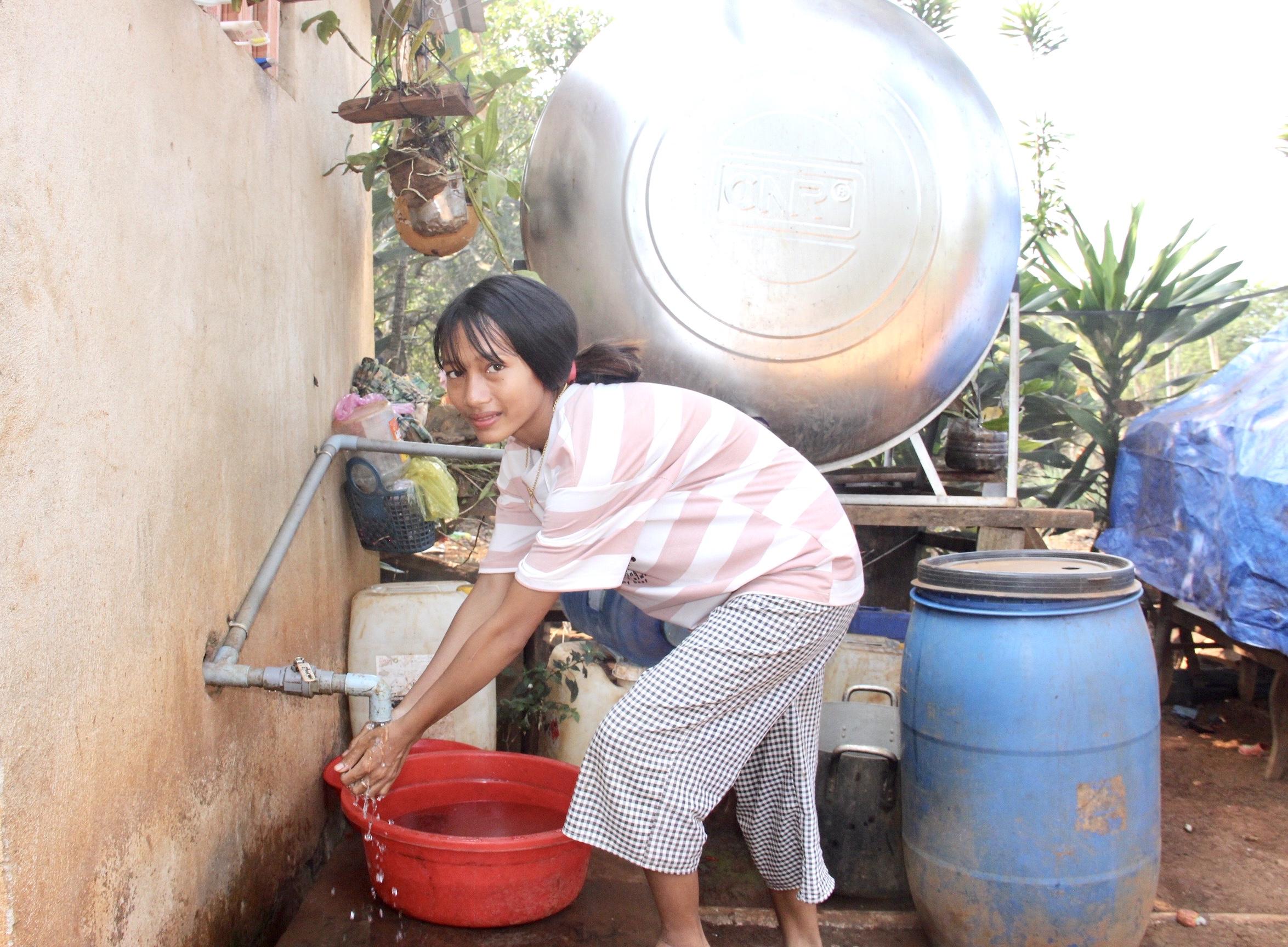 Một thiếu nữ đồng bào S'tiêng vui mừng khi được Đoàn Kinh tế - Quốc phòng 778 và các lực lượng cấp nước miễn phí
