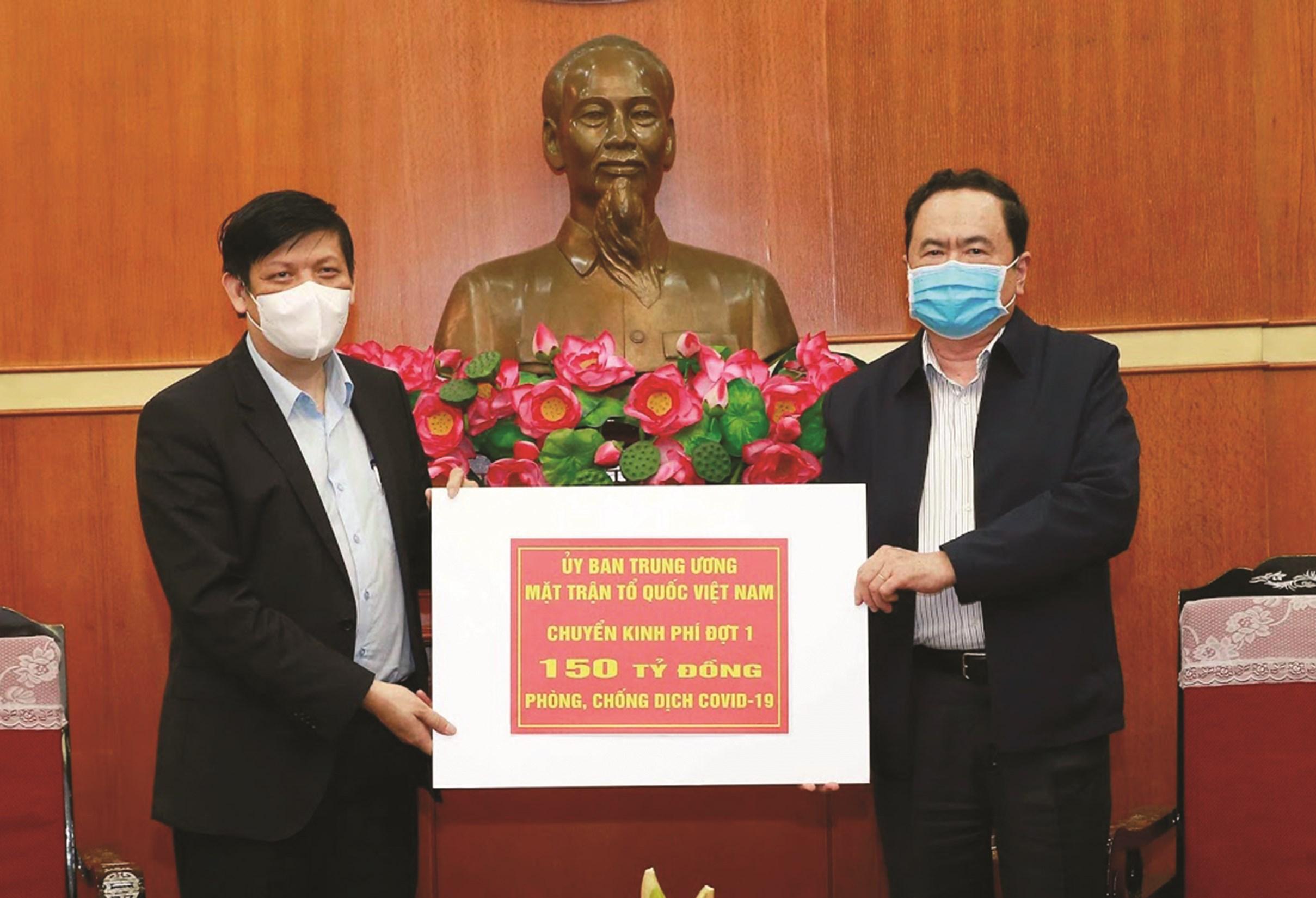 Chủ tịch Ủy ban Trung ương MTTQ Việt Nam Trần Thanh Mẫn (bên phải) trao số tiền phân bổ đợt 1 cho Bộ Y tế để phòng chống dịch
