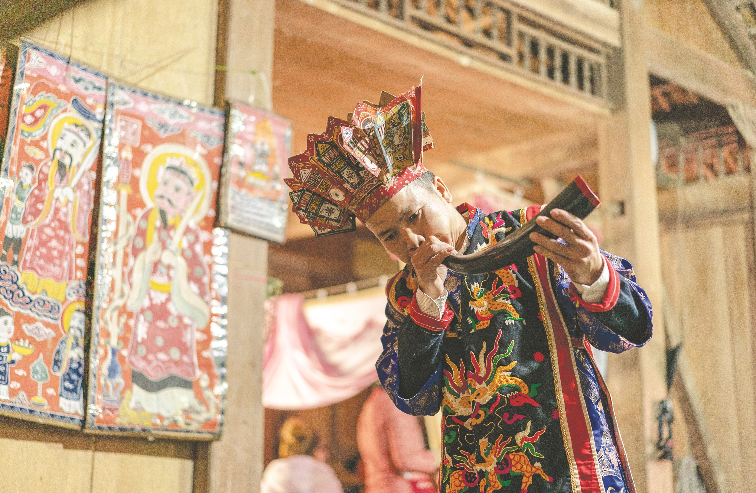 Thầy cúng thổi tù và để mời gọi Ngọc Hoàng xuống chứng giám nghi lễ cấp sắc.