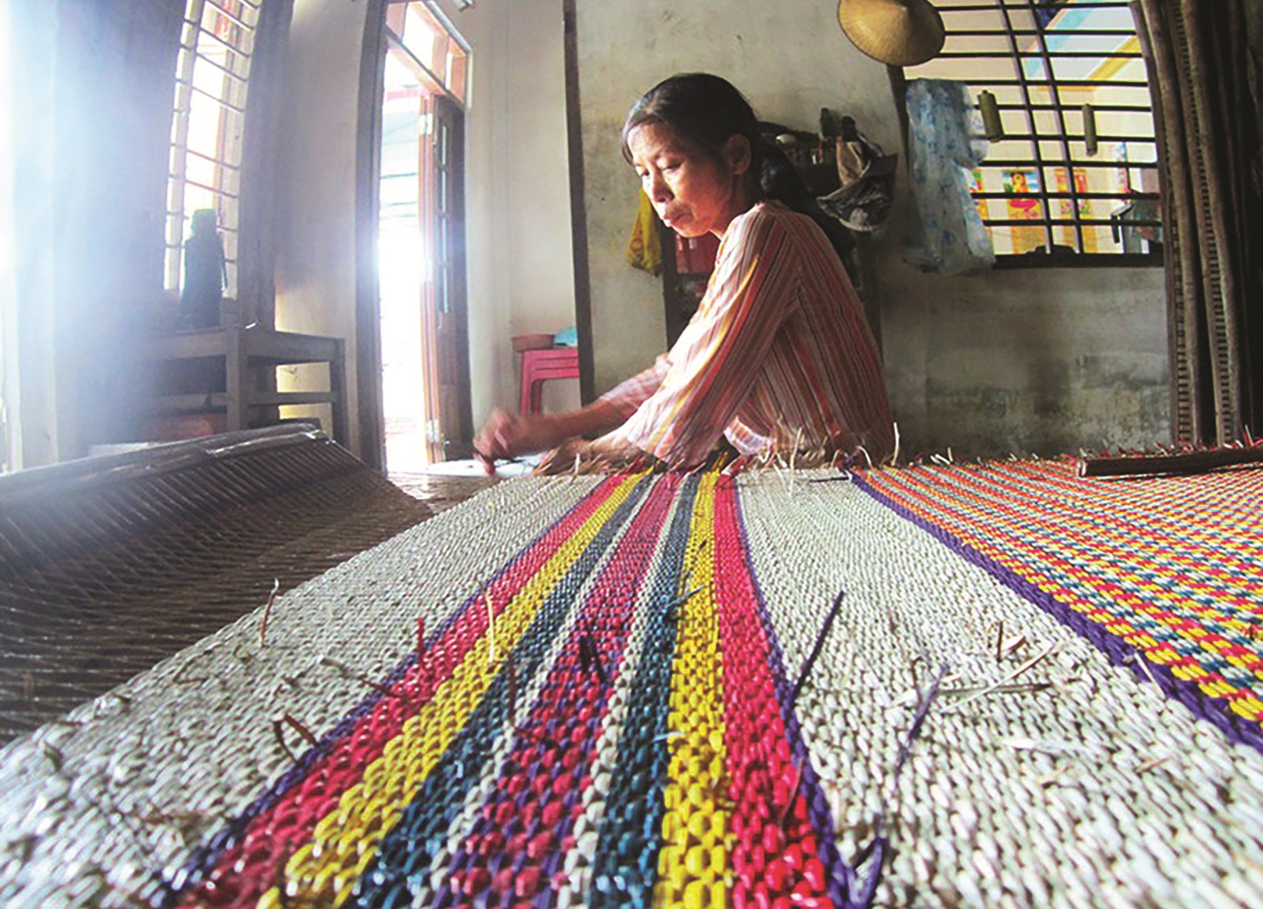 """Dù công việc đan chiếu thủ công vất vả, thu nhập chẳng là bao, nhiều phụ nữ làng An Xá vẫn tâm huyết """"giữ lửa"""" với nghề. (Ảnh: Trung Hiếu)."""
