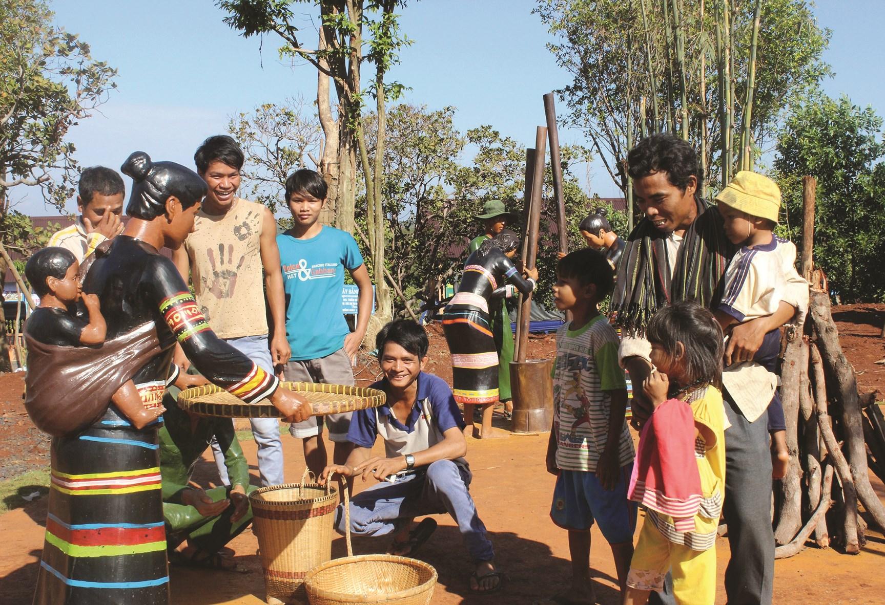 Người dân Bom Bo vui mừng bên hình ảnh tái hiện tiếng chày giã gạo. (Ảnh Bùi Liêm)