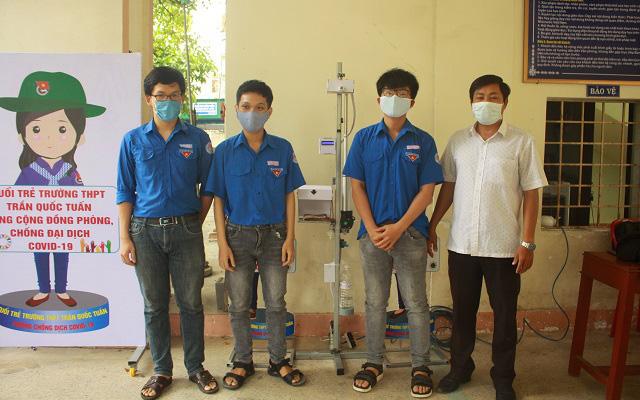 Nhóm ba em học sinh và thầy giáo hướng dẫn Phan Đình Phúc bên thiết bị đo thân nhiệt và rửa tay tự động Trường THPT Trần Quốc Tuấn.