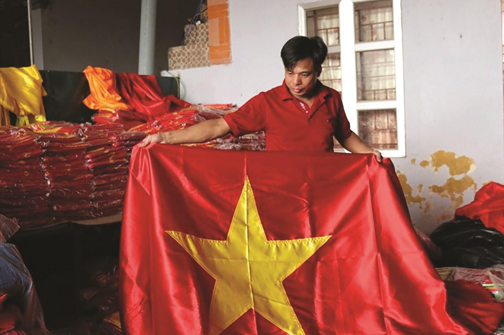 Anh Nguyễn Văn Phục (làng Từ Vân) kiểm tra lá cờ Tổ quốc sau khi vừa hoàn thiện sản phẩm