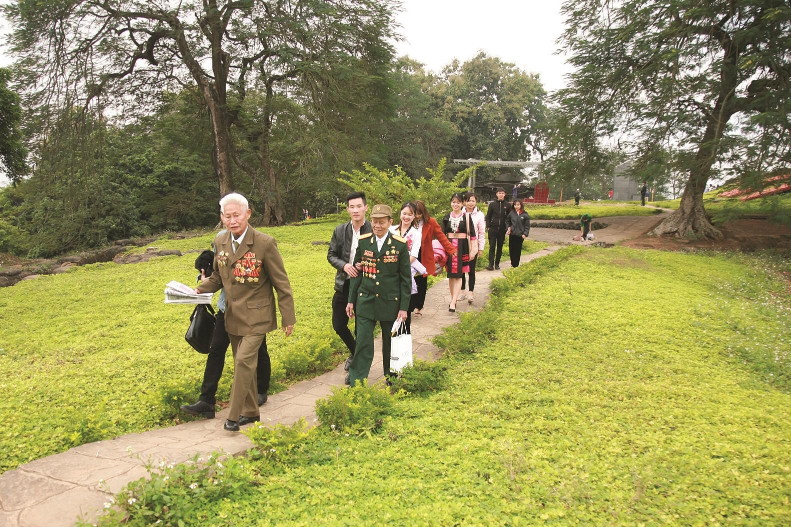 Cựu chiến binh Phạm Bá Miều (người đội mũ) trong chuyến thăm di tích đồi A1