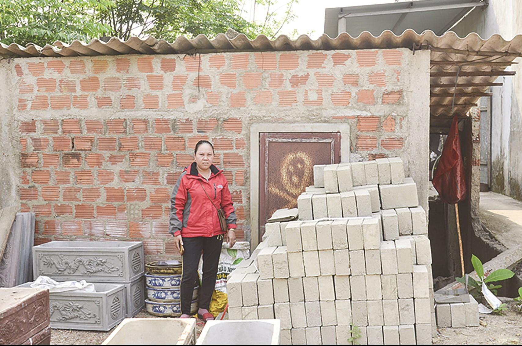 Bà Lê Thị Kiều (vợ ông Trinh) bên ngôi nhà bị ông Lê Hữu Phước xây dựng lấp lối vào.