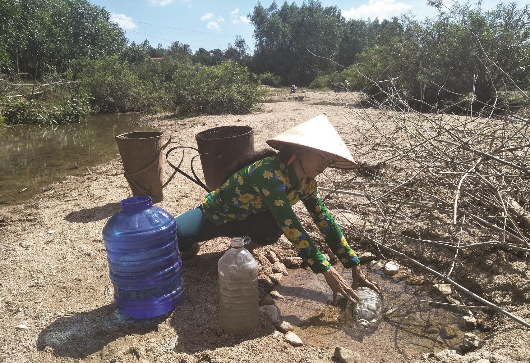 Người dân Vân Canh thiếu nước sinh hoạt phải ra suối múc từng can nước về dùng