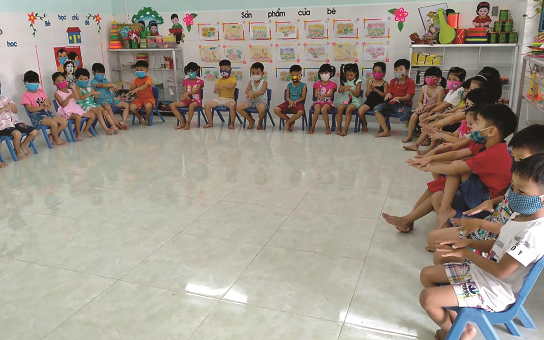 Các bé mẫu giáo được cô giáo hướng dẫn cách đeo khẩu trang đúng cách