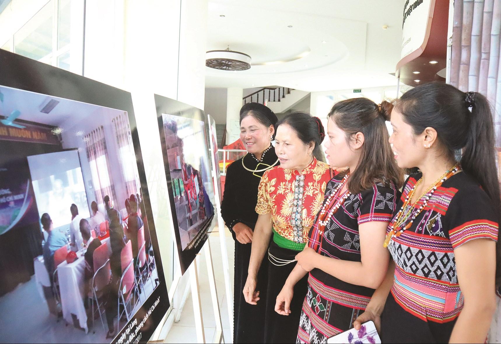 Bà Lò Thị Tóm (thứ 2 từ trái sang) xem Triển lãm ảnh về Bác Hồ tại Làng Văn hóa, Du lịch các dân tộc Việt Nam
