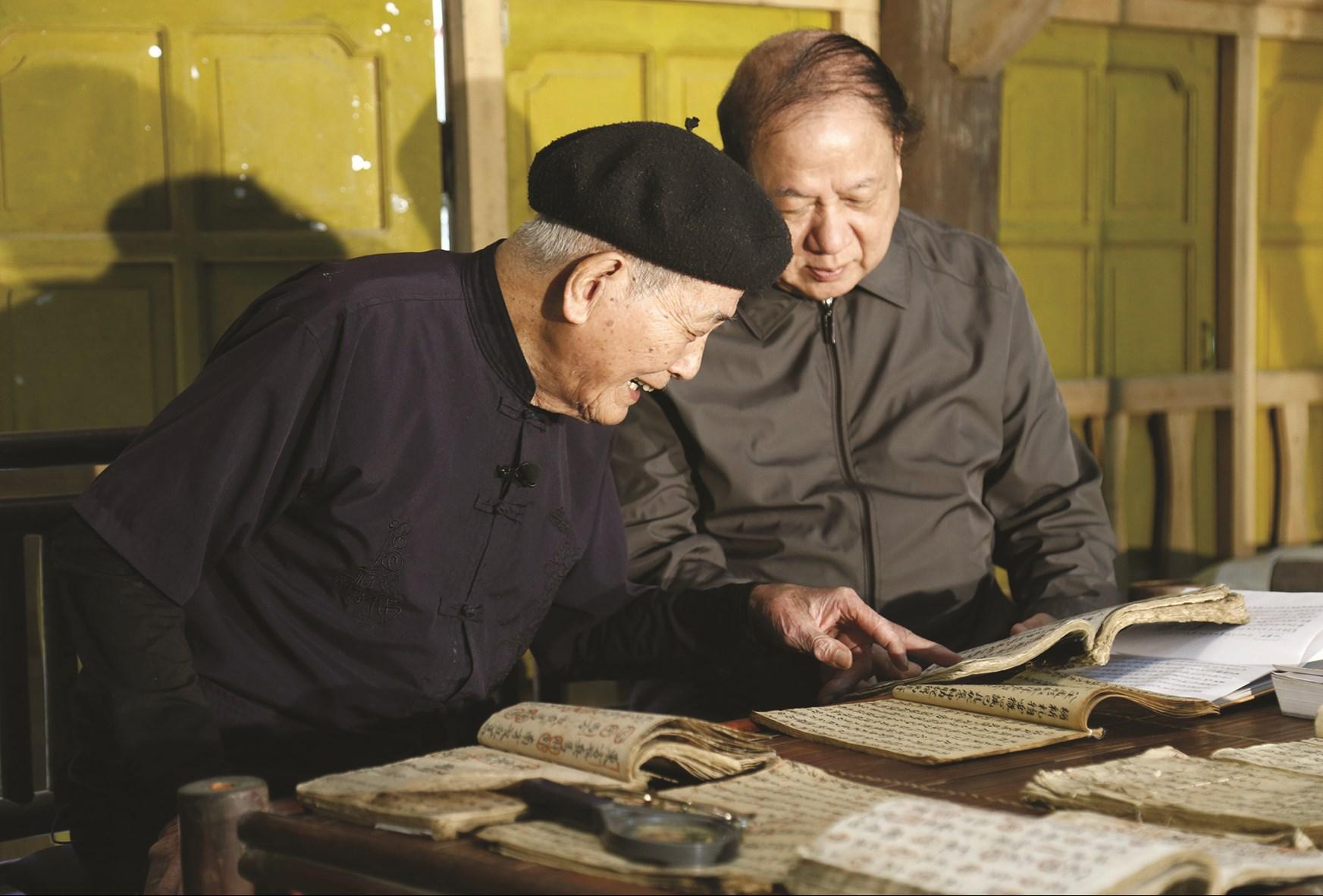 Nghệ nhân Lương Long Vân (bên trái) luôn say mê nghiên cứu biên dịch chữ Nôm Tày