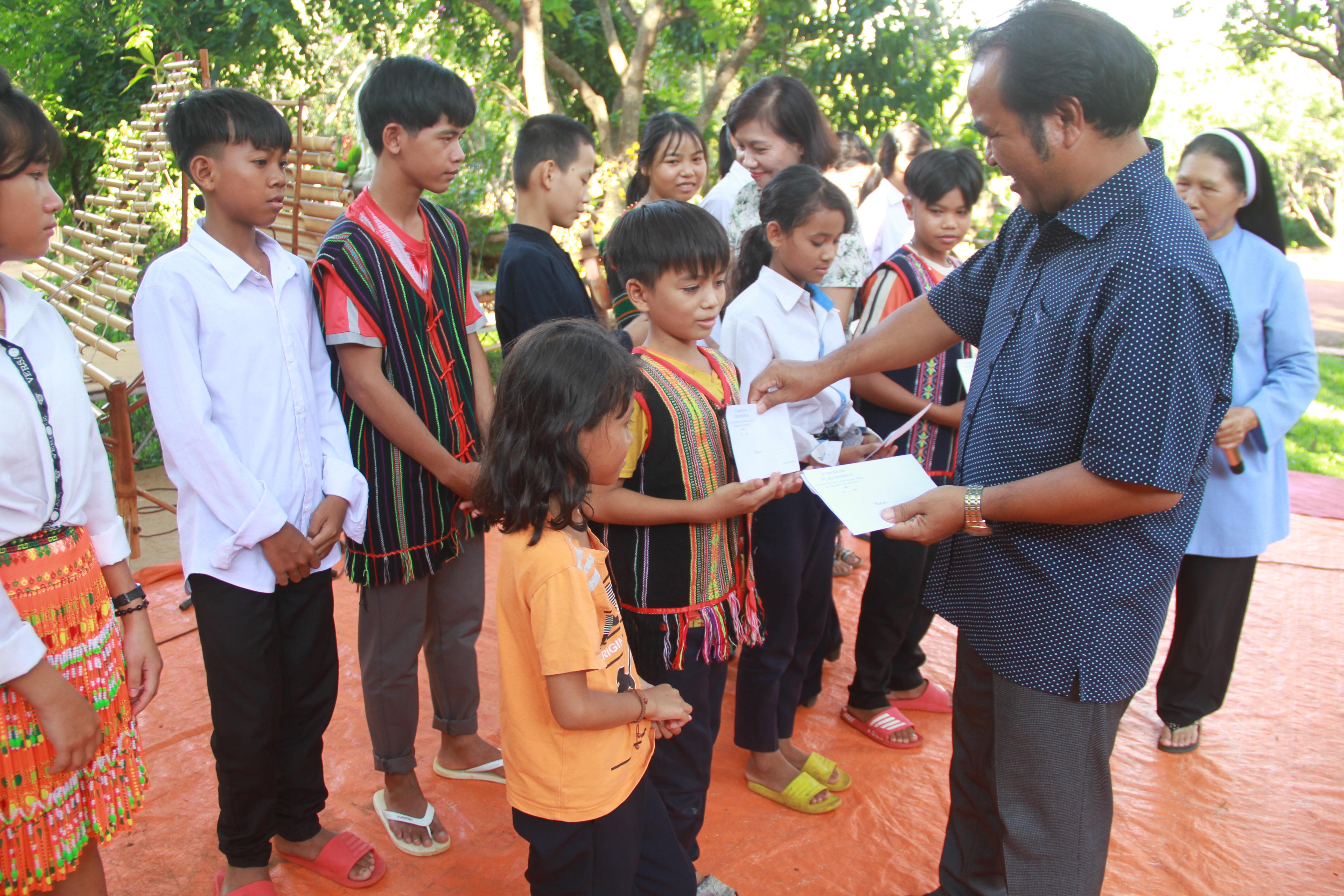 Ông Điểu Mưu, Phó Vụ trưởng Vụ Địa Phương II trao quà cho các em học sinh