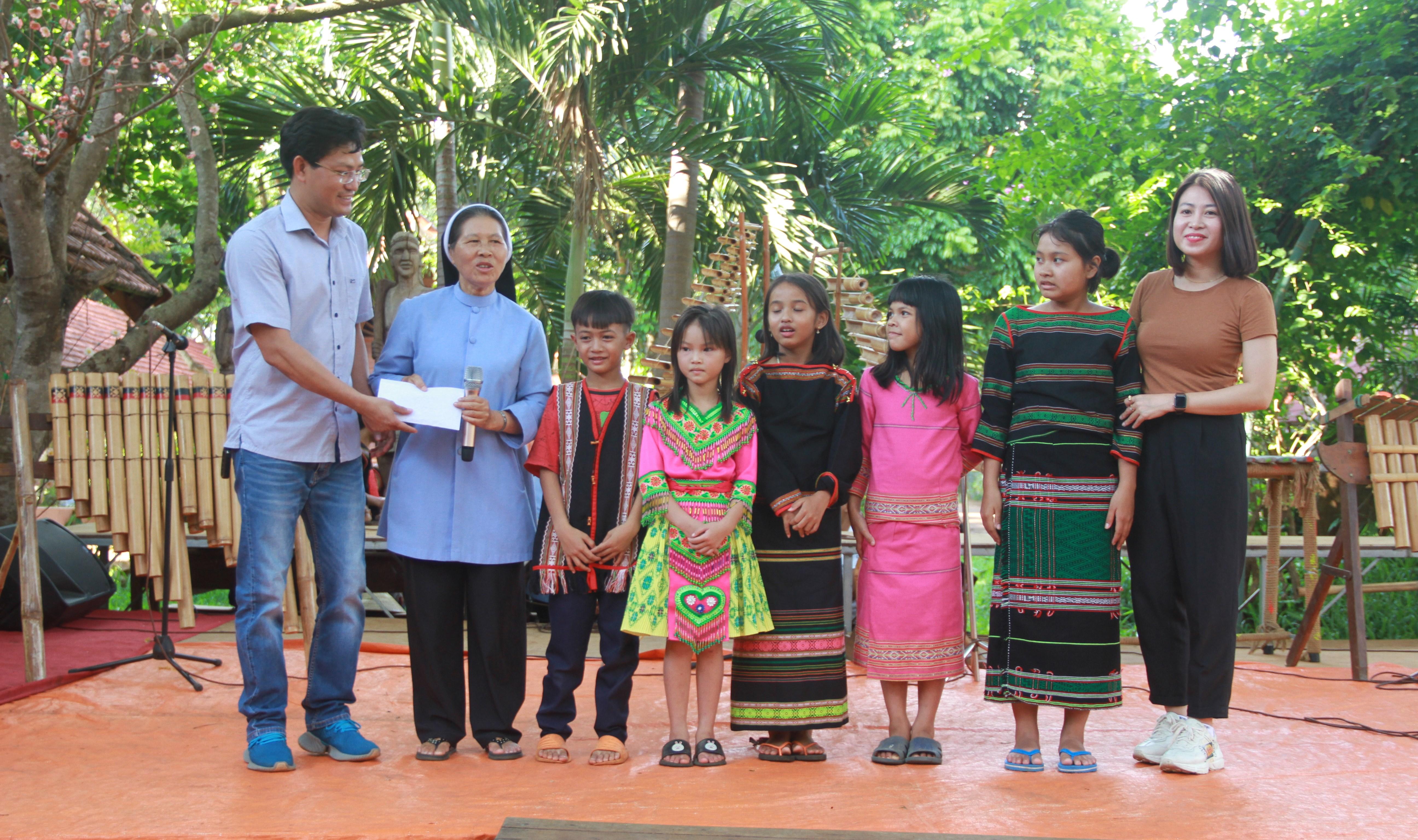 Đại diện Công ty HBT (bìa trái) tặng quà cho các em học sinh nghèo.