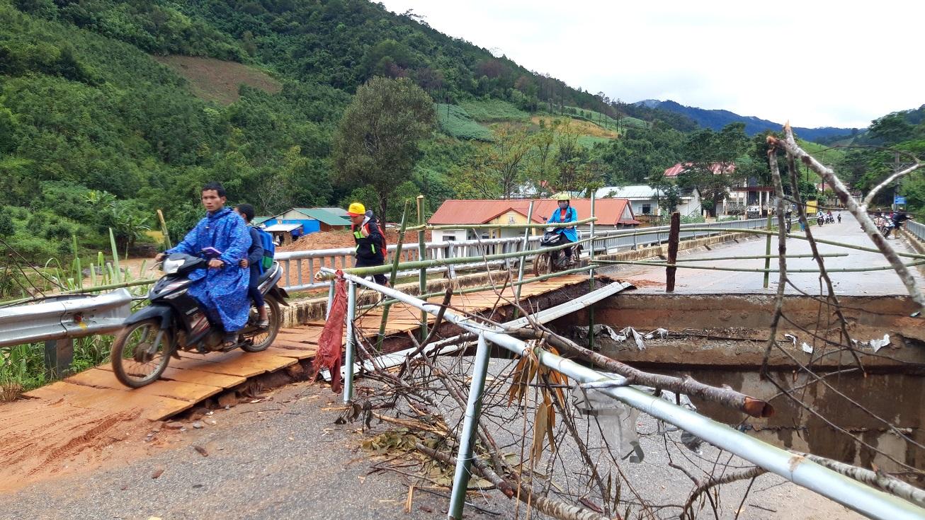 """Cây cầu bắc qua sông Pô Kô bị """"đứt"""" một đoạn, người dân phải bắc cầu tạm bằng ván để di chuyển qua lại"""